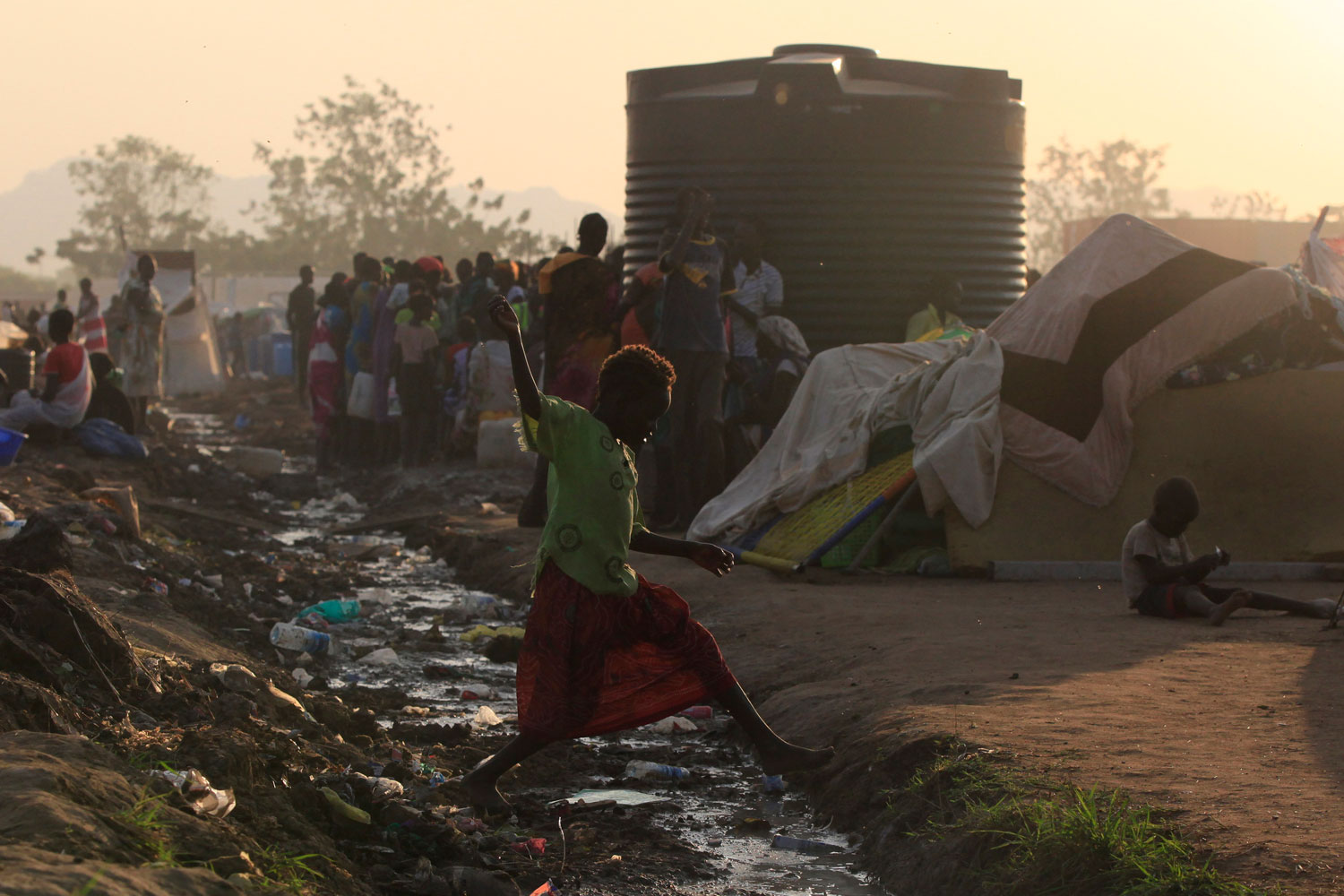 Jan. 10, 2014. A barefoot girl jumps over an open drain filled with rubbish at Tomping camp in Juba, South Sudan.