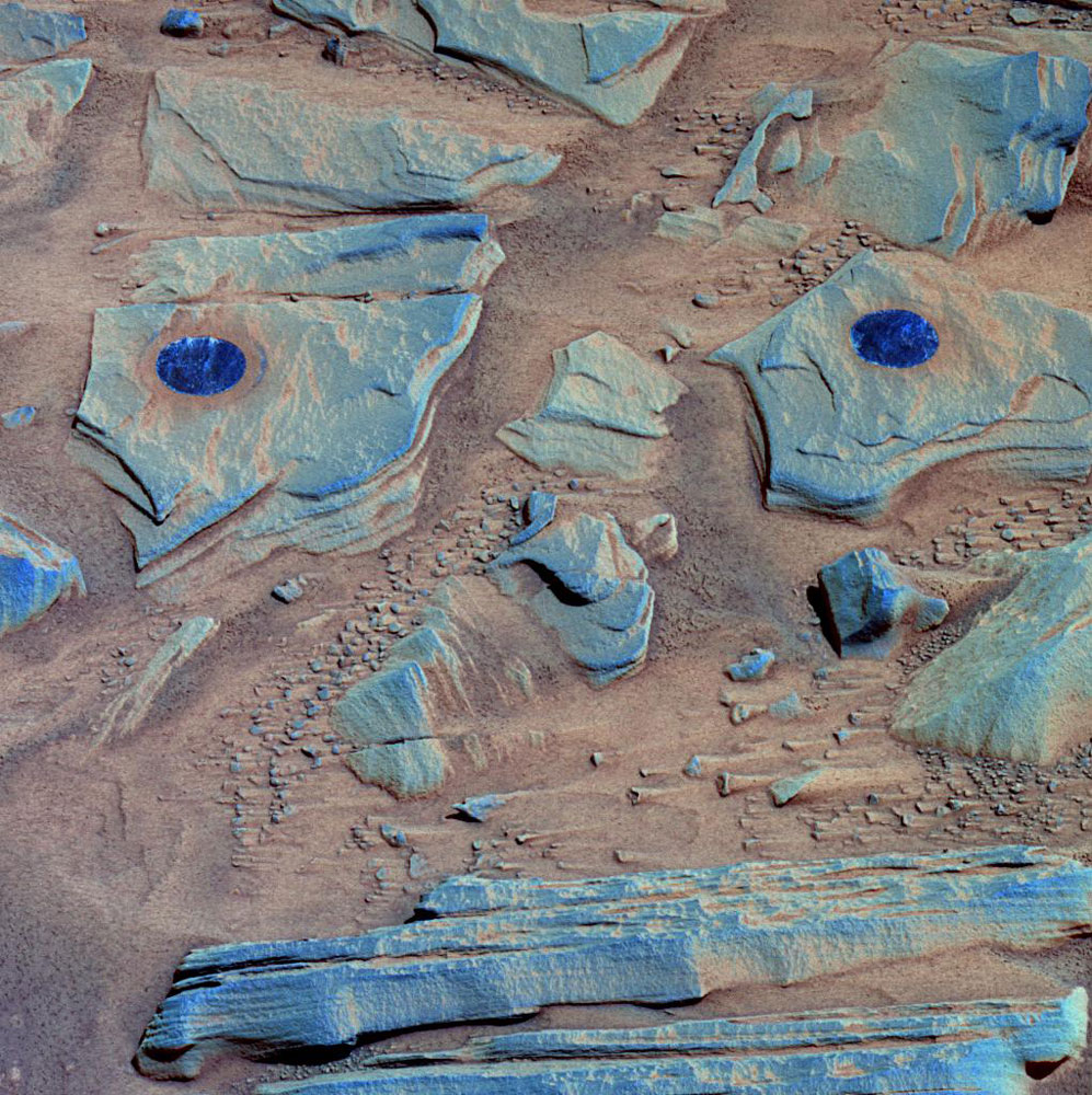"NASA's Spirit rover acquired this false-color image after using its abrasion tool to brush the surfaces of rock targets informally named ""Stars"" (left) and ""Crawfords"" (right). Small streaks of dust extend for several centimeters behind the chips and pebbles in the dusty soil."