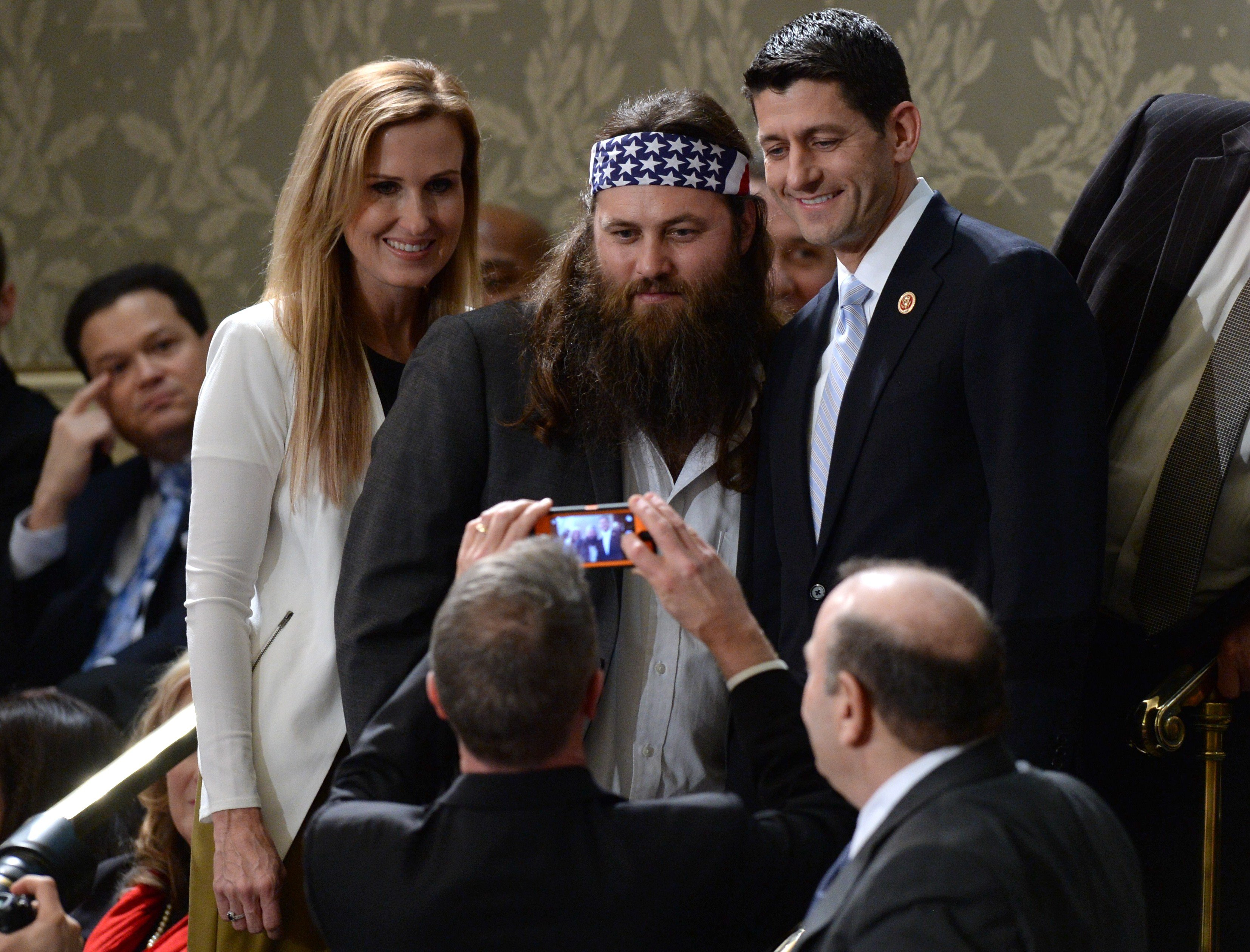 Willie Robertson of the television show Duck Dynasty and his wife Korie Robertson pose for a picture with Republican Representative from Wisconsin Paul Ryan.