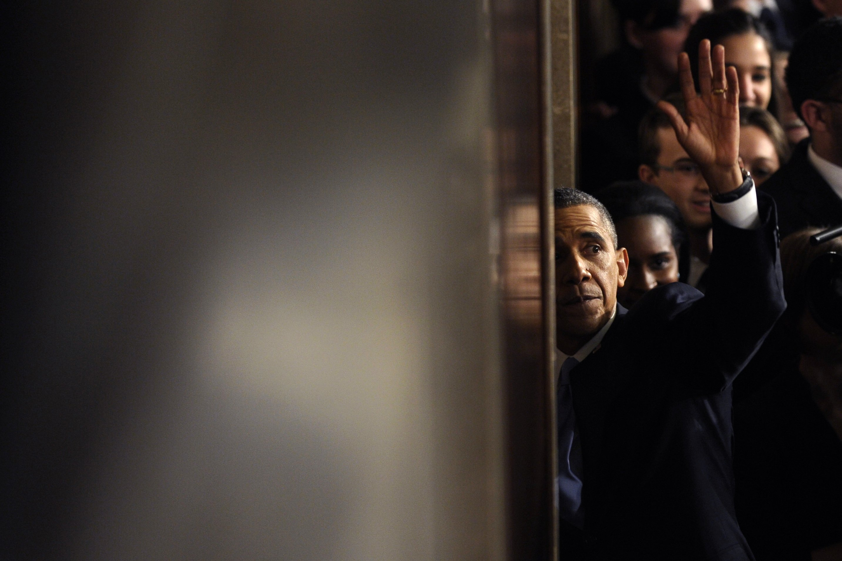 President Barack Obama waves as he walks through a door to leave the House chamber after giving his State of the Union address.