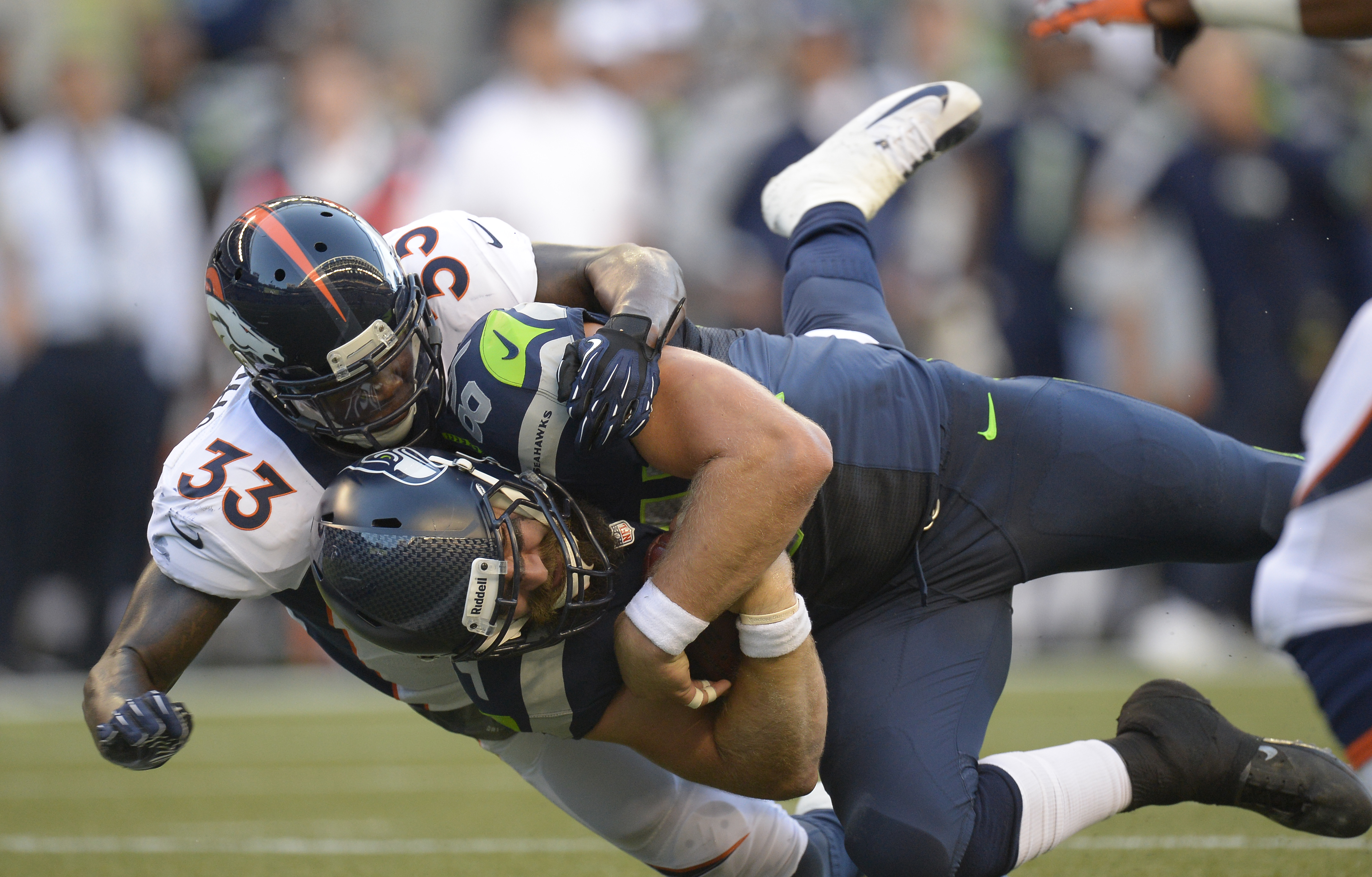 Seattle Seahawks tight end Sean McGrath (84) gets wrapped up by Denver Broncos safety Duke Ihenacho (33) after a gain during the first quarter, on Aug. 17, 2013 at Century Link Field in Seattle.