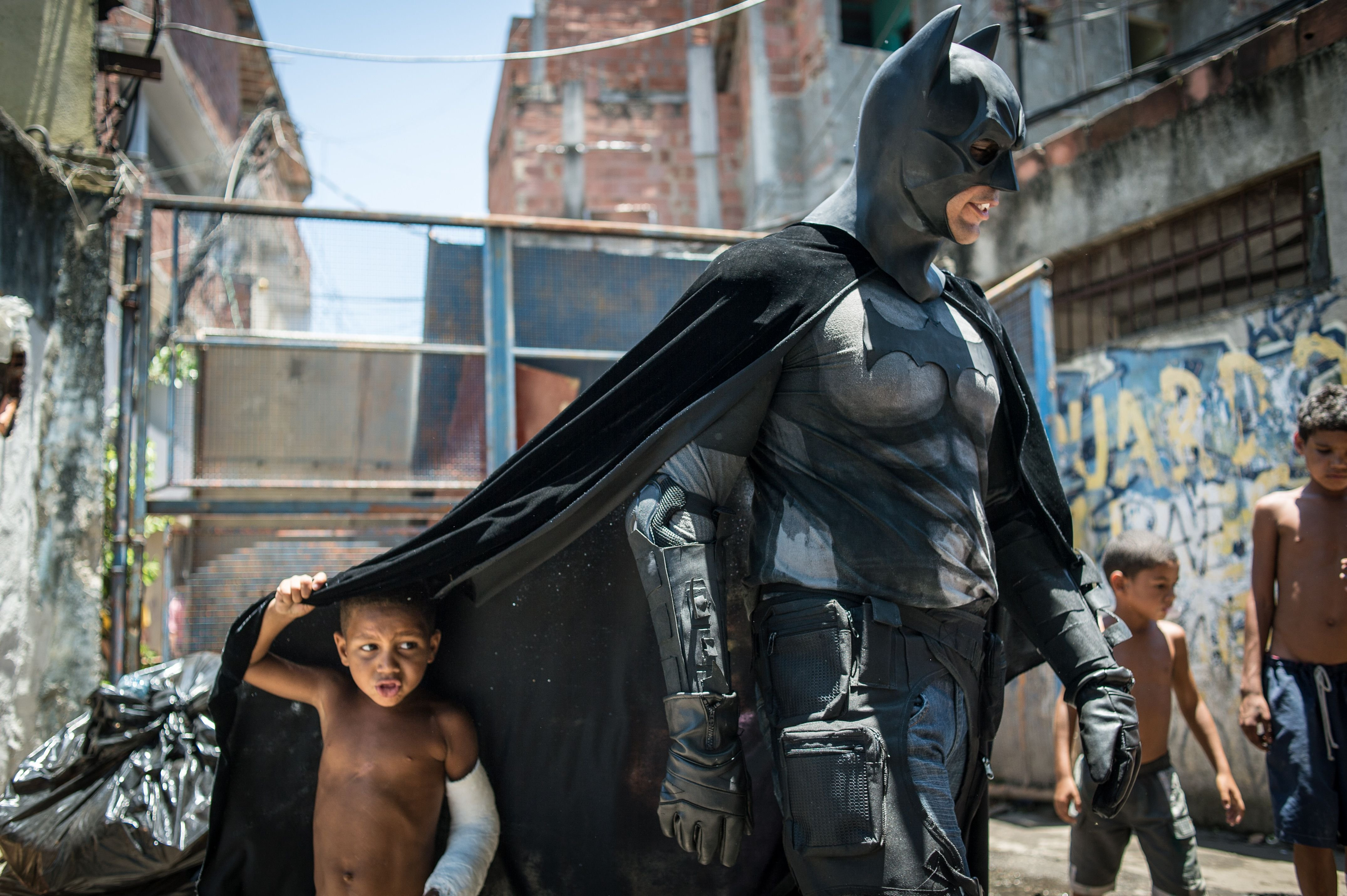 Children play around a man disguised as Batman in the Favela do Metro slum in Rio de Janeiro, Jan. 9, 2014. Families living in this shantytown within a stone's throw of Rio 's mythical Maracana stadium refuse to have their homes demolished as part of a project to renovate the district before the FIFA World Cup circus pitches camp in June.