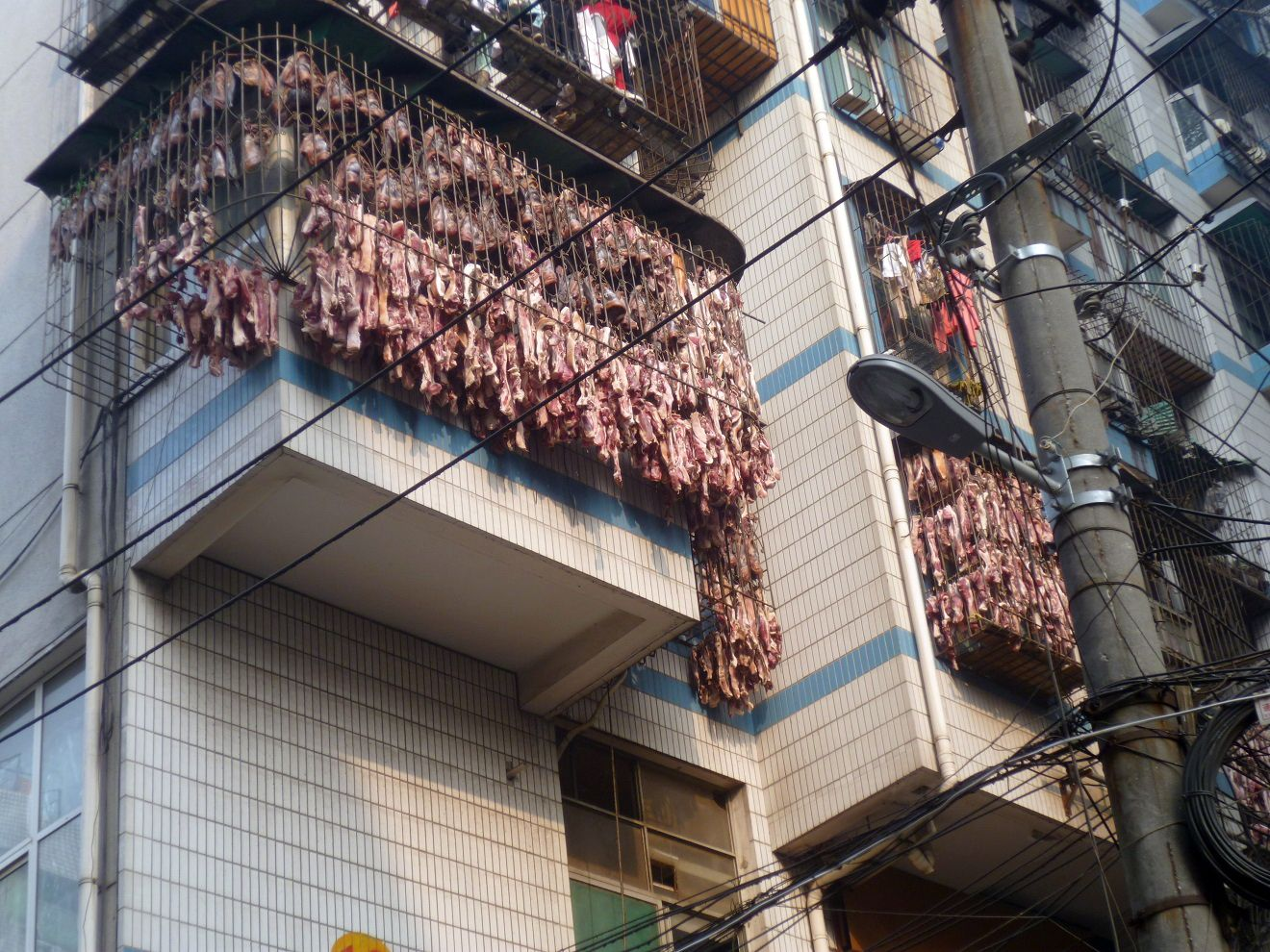 Bacon hangs to dry from a third-floor apartment window in Wuhan, China, Jan. 9, 2014.
