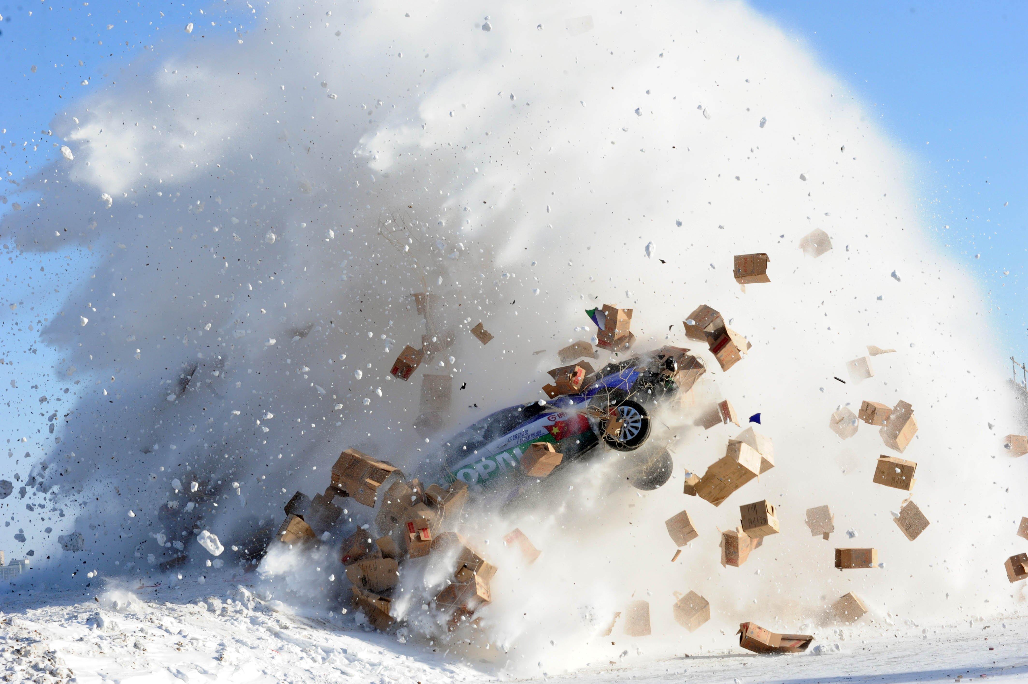 Daredevil Xie Yujun leaps over the frozen Heilongjiang River in a stunt car in Heihe, north China's Heilongjiang province, Jan. 12, 2014.