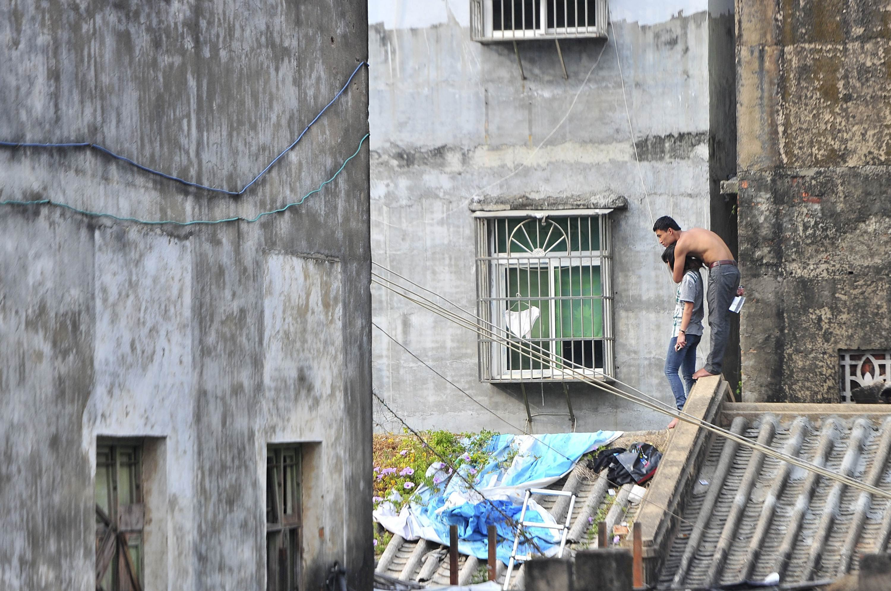 A topless man holds his girlfriend hostage with a knife atop a residential building in Sanya, Hainan province, Jan. 20, 2014. According to local media, the man, surnamed Lin, held his girlfriend hostage to threaten both families into allowing their marriage. Lin stood off with police on the roof for several hours and was arrested soon after he got down the building.