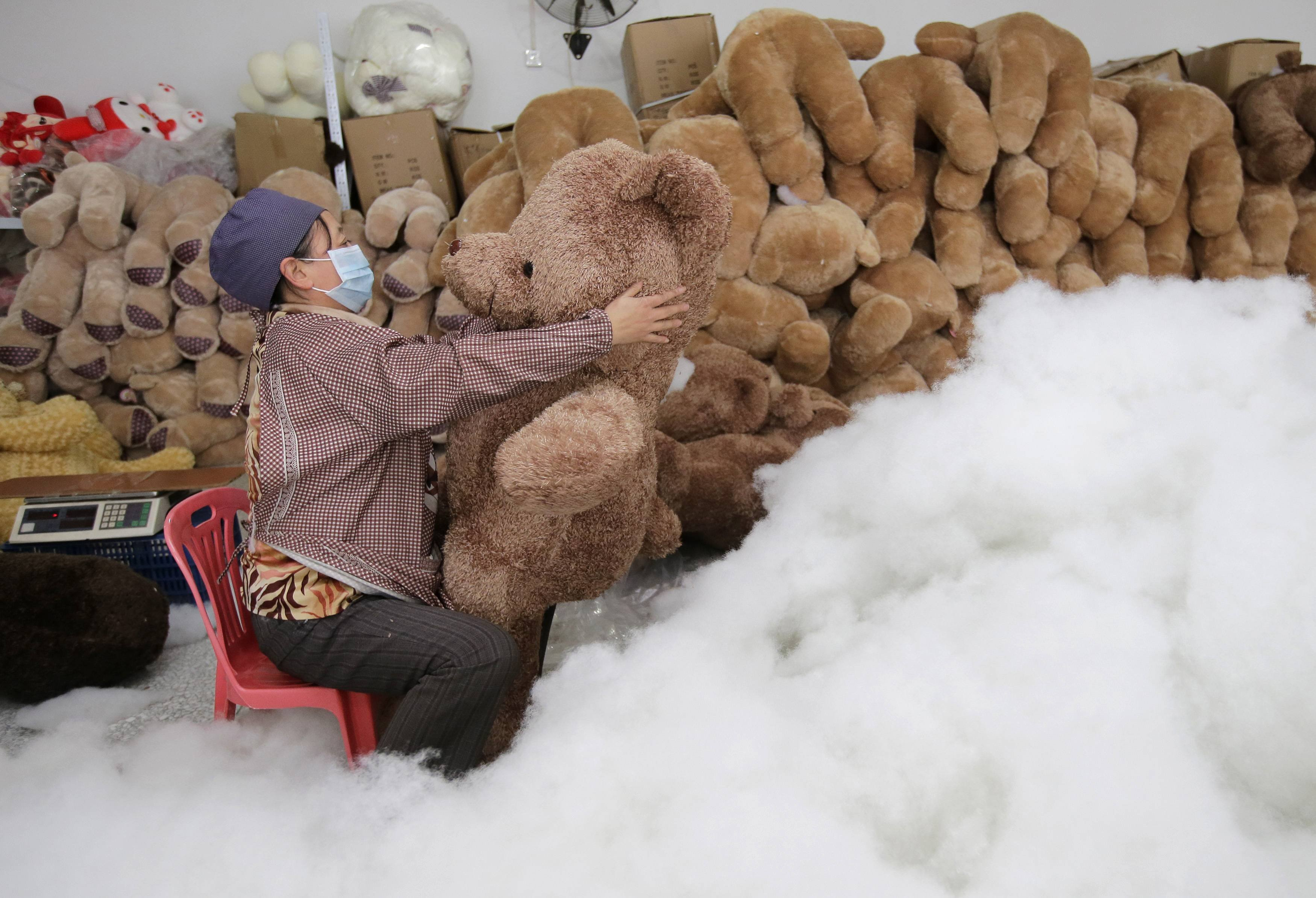 A worker stuffs a toy bear with cotton at a toy factory in Wuhan, Hubei province, Jan. 15, 2014.