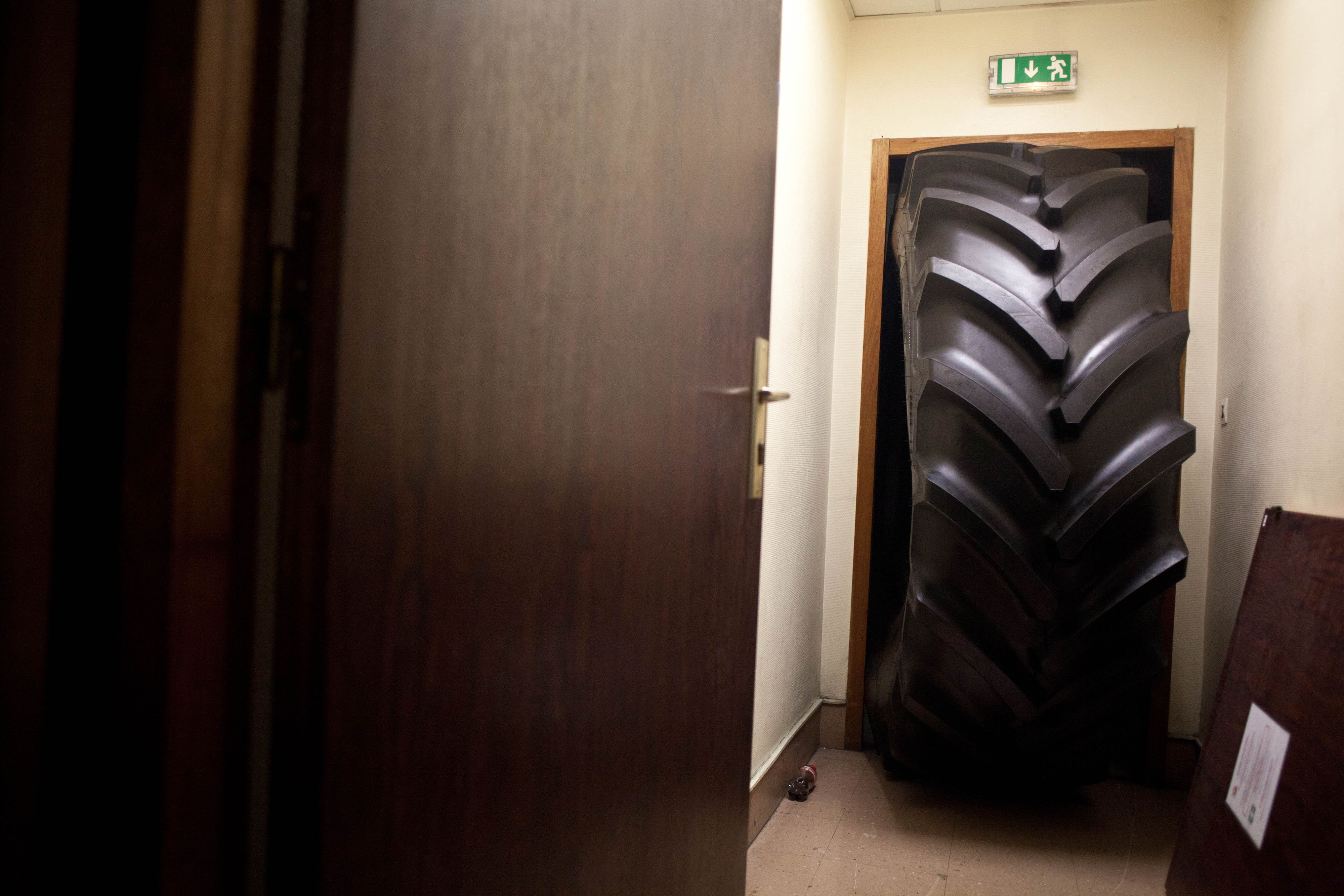 A huge tire blocks the door where Goodyear Factory production workers, Michel Dheilly and Bernard Glesser, were being detained by workers, Jan. 6, 2014, in Amiens, France.