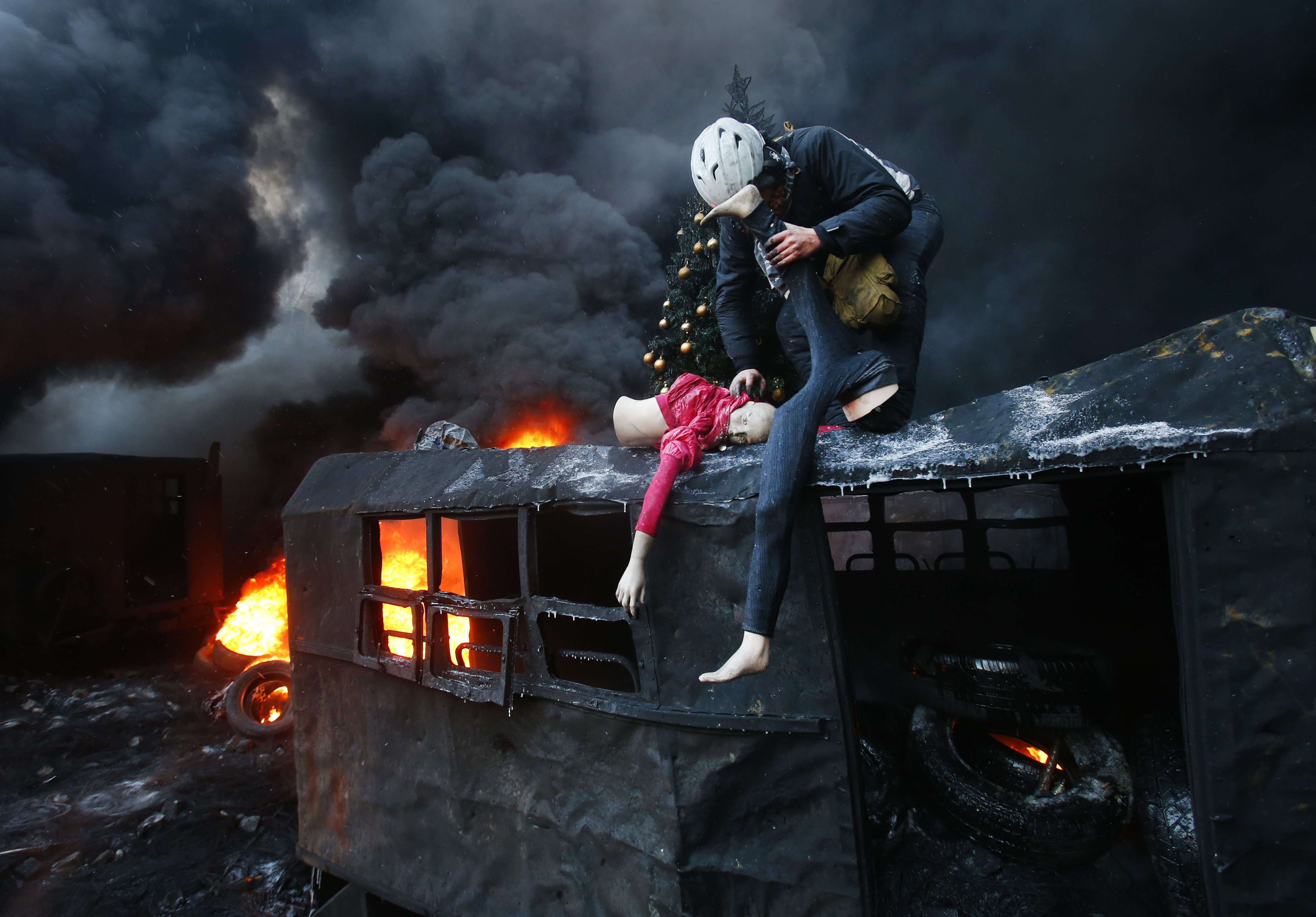 A protester breaks up a mannequin on the roof of the burned truck during clashes with police in central Kiev, Ukraine, Thursday Jan. 23, 2014.