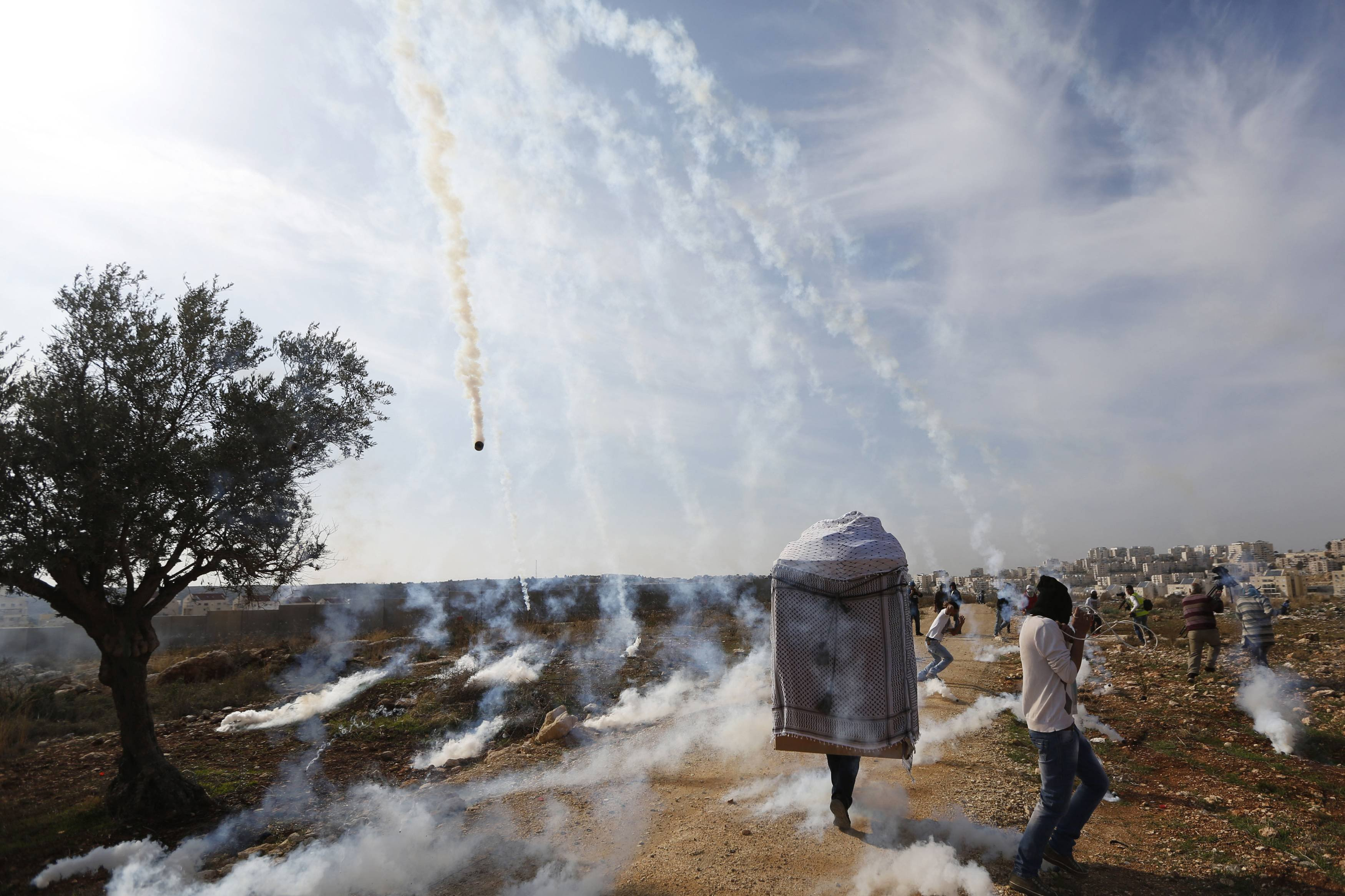 A man wearing a large puppet head and Palestinian stone-throwing protesters run as tear gas is fired by Israeli soldiers during clashes at a weekly demonstration against Jewish settlements in the West Bank village of Bilin, near Ramallah Jan. 3, 2014.