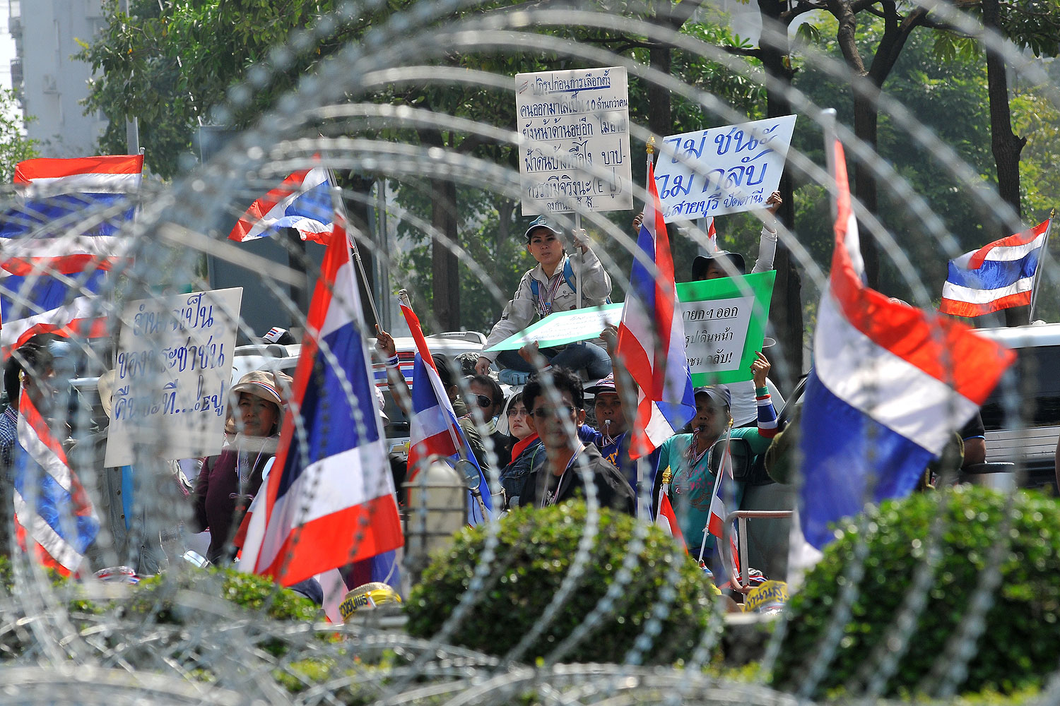 Anti-government protesters wave national flags as they block the street in front of the Office of the Defence Permanent Secretary during a rally in Bangkok on Jan. 22, 2014