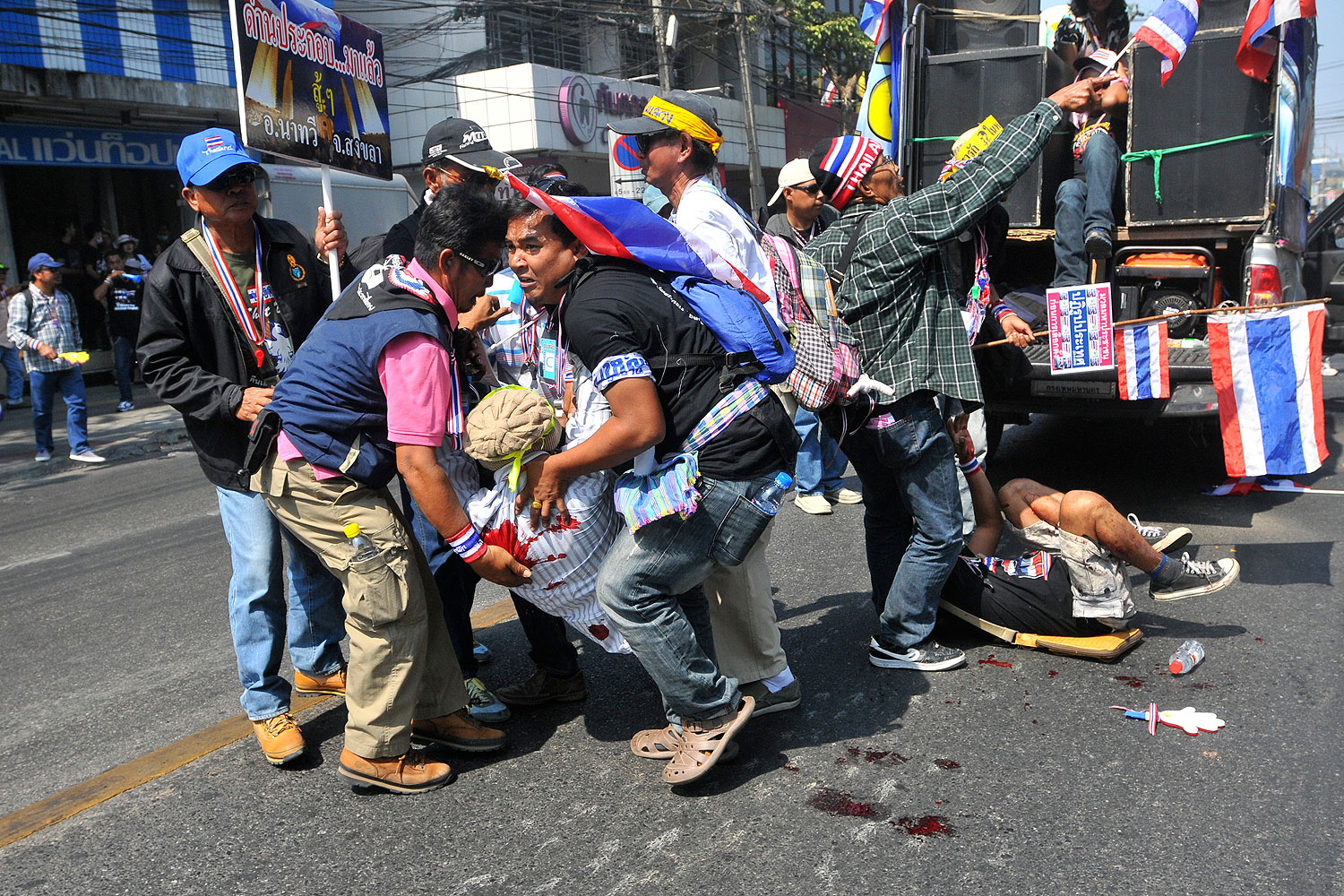 Anti-government protesters help a fellow protester injured in a grenade attack during a rally in Bangkok Jan. 17, 2014