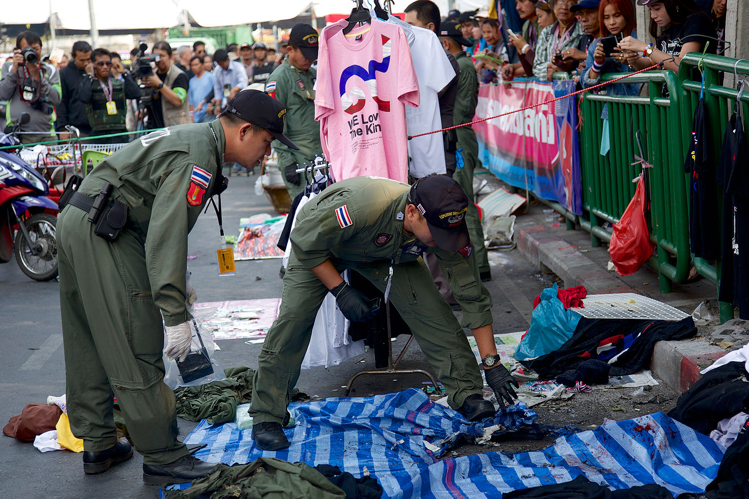 Thai police officers examine the scene of an explosion at an antigovernment protest site in Bangkok on Jan. 19, 2014
