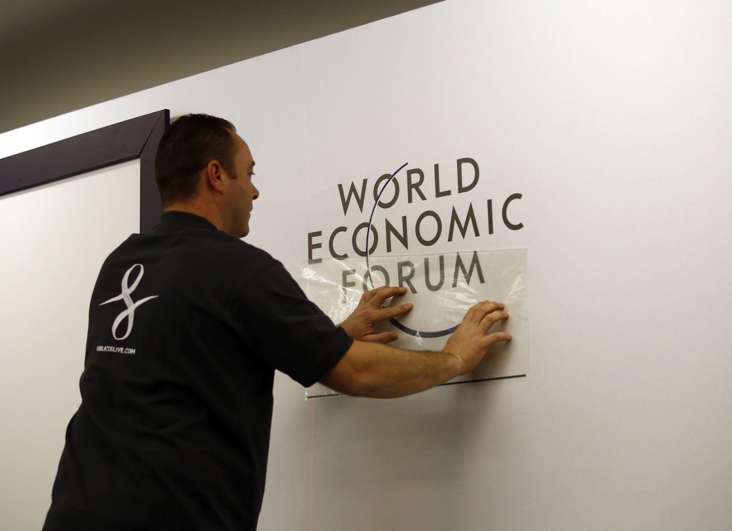 A worker prepares a logo for the World Economic Forum inside the Congress Center ahead of the World Economic Forum 2014 (WEF) meeting in Davos, Switzerland, on Sunday, Jan. 19, 2014.