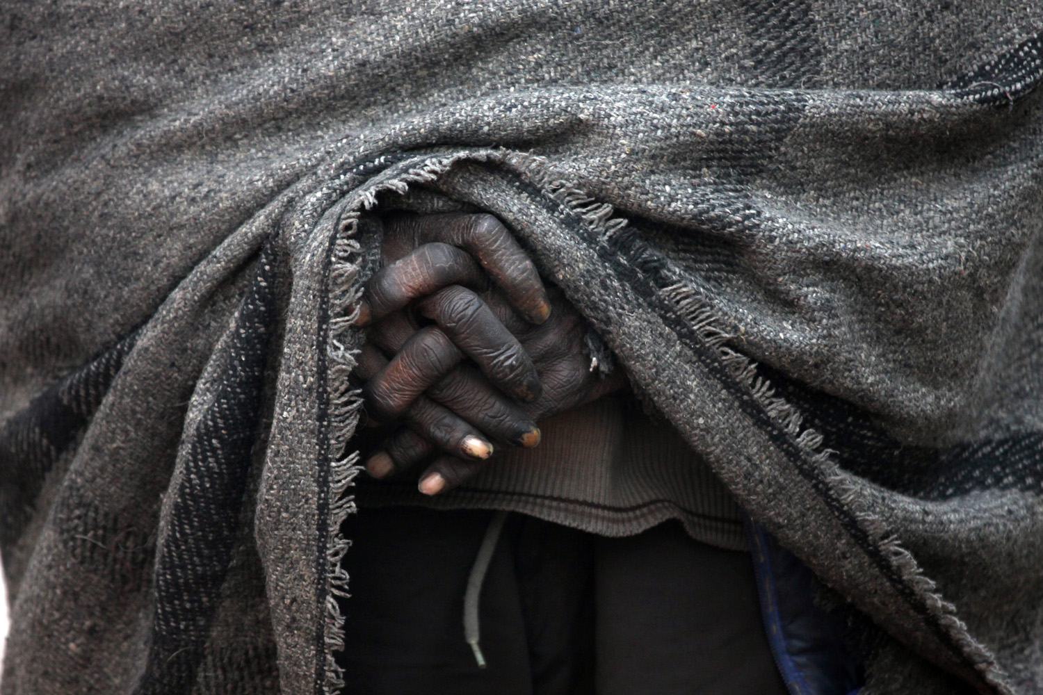 Dec. 30, 2013. An Indian daily wage laborer wrapped in a blanket warms himself near a fire (unseen) on a cold morning in Amritsar, India.