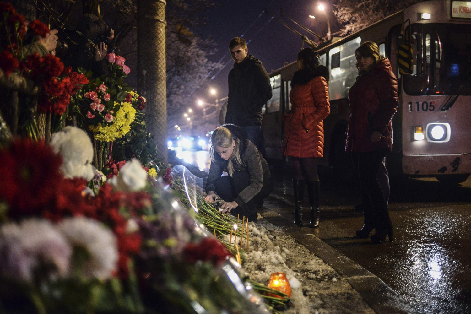 Dec. 31, 2013. A woman places flowers at the site of an explosion on a trolleybus that climed the lives of 33 people, in Volgograd, Russia.