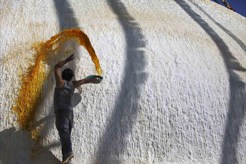 Jan. 1, 2014. A Buddhist man splashes coloured water on the dome of Boudhanath Stupa in Kathmandu, Nepal.