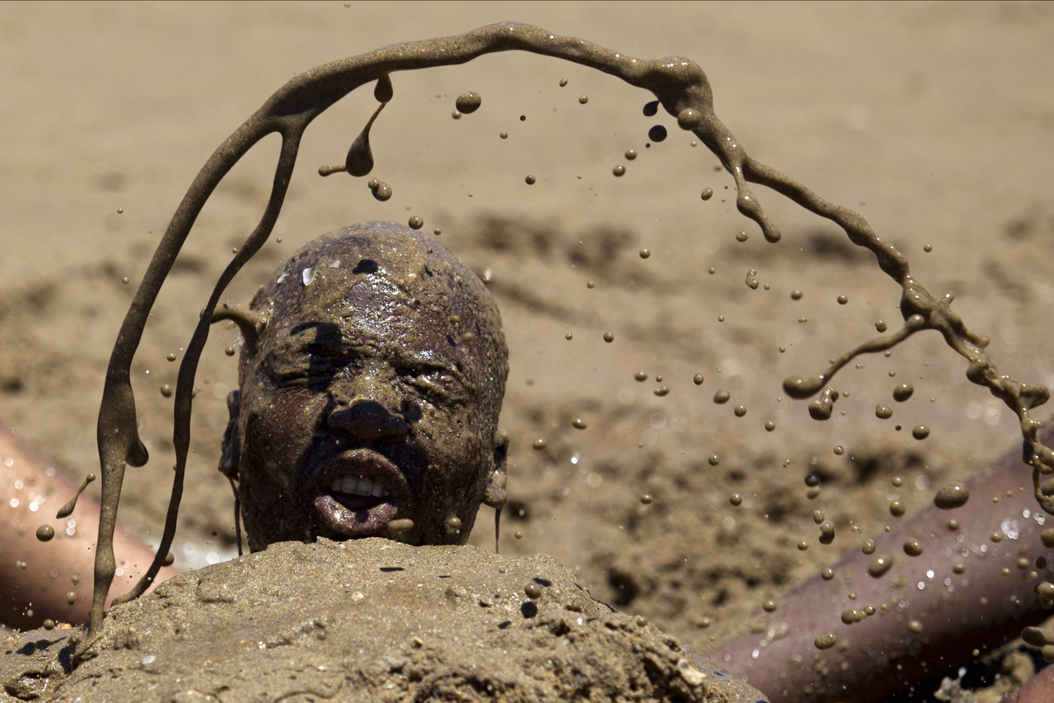 Jan. 1, 2014. A man received a sand bath from friends as thousands of people took to the beaches on New Year's Day in Durban, South Africa.