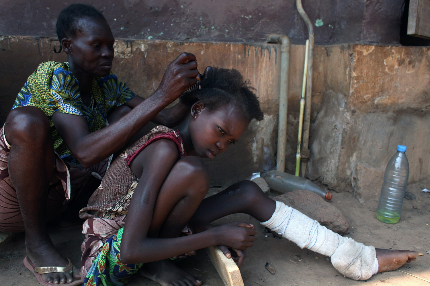 Jan. 1, 2014. A woman, displaced as a result of religious violence, plaits the hair of her daughter who is nursing an injury at a hospital in Bossangao, Central African Republic.