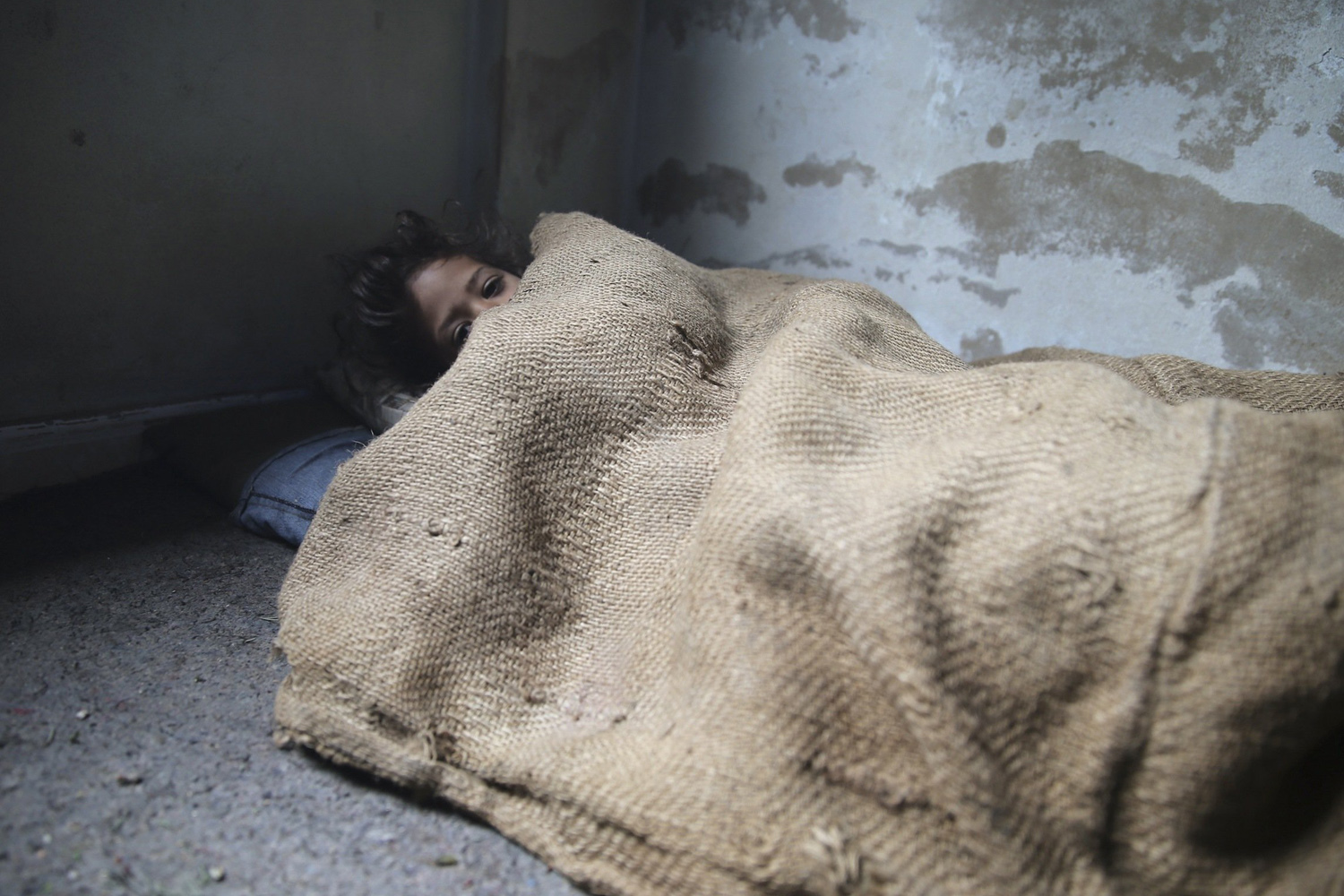 Jan. 6, 2014. A girl covers herself with sackcloth due to a shortage of blankets in eastern Ghouta, near Damascus.