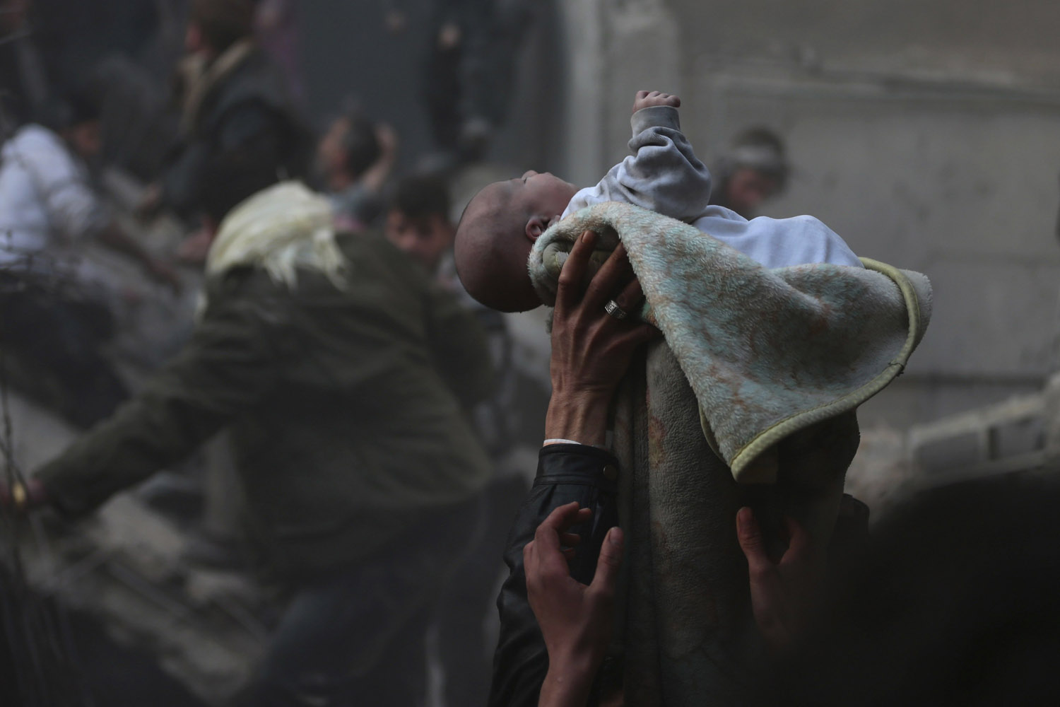 Jan. 7, 2014. Men hold up a baby who survived what activists say was an airstrike by forces loyal to Syrian President Bashar al-Assad in the Duma neighbourhood of Damascus.