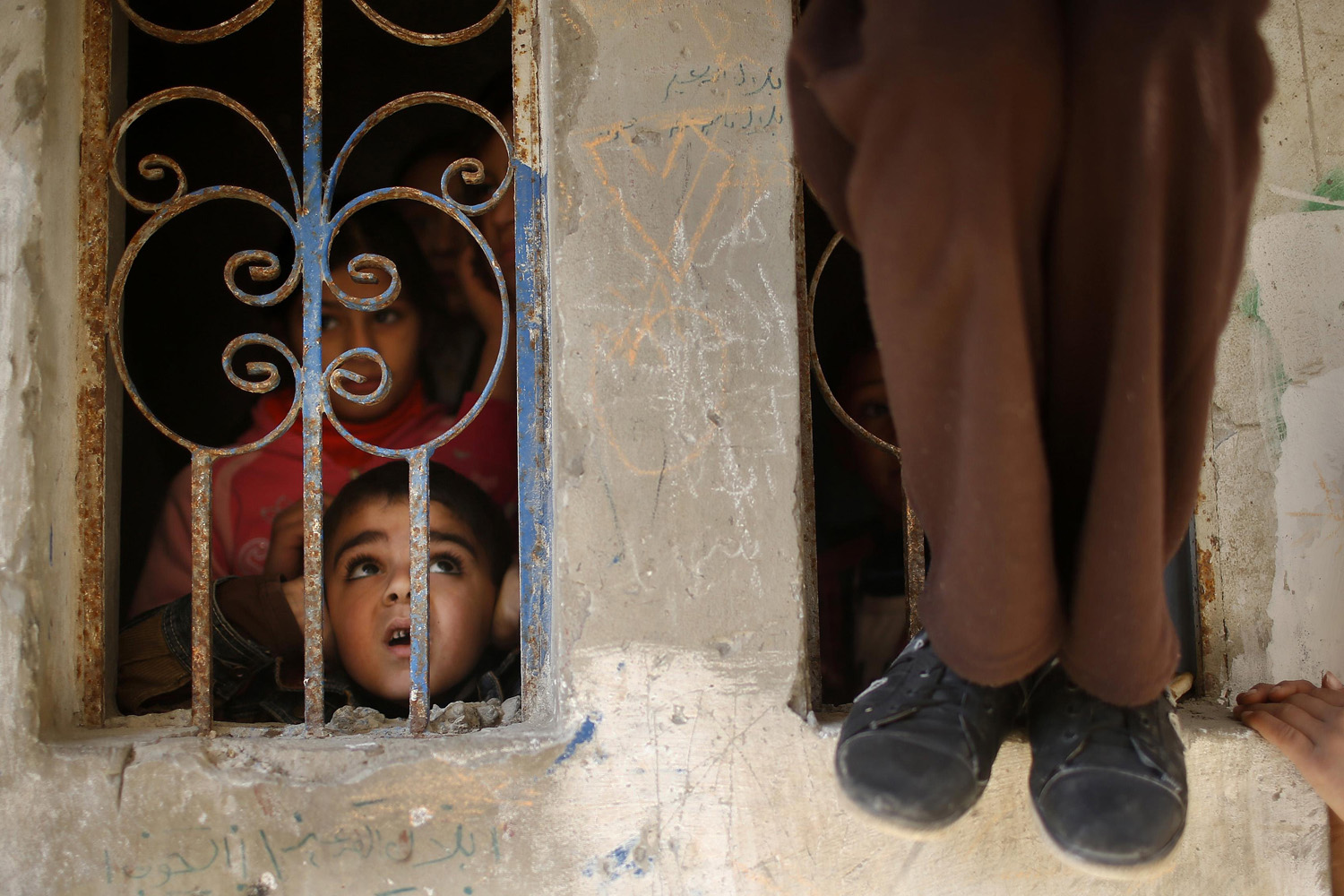 Jan. 8, 2014. A Palestinian boy covers his ears as a militant fires a weapon in the air during the funeral of 32-year-old Palestinian Islamic Jihad militant Mohammed Salama al-Ijla in Gaza City.