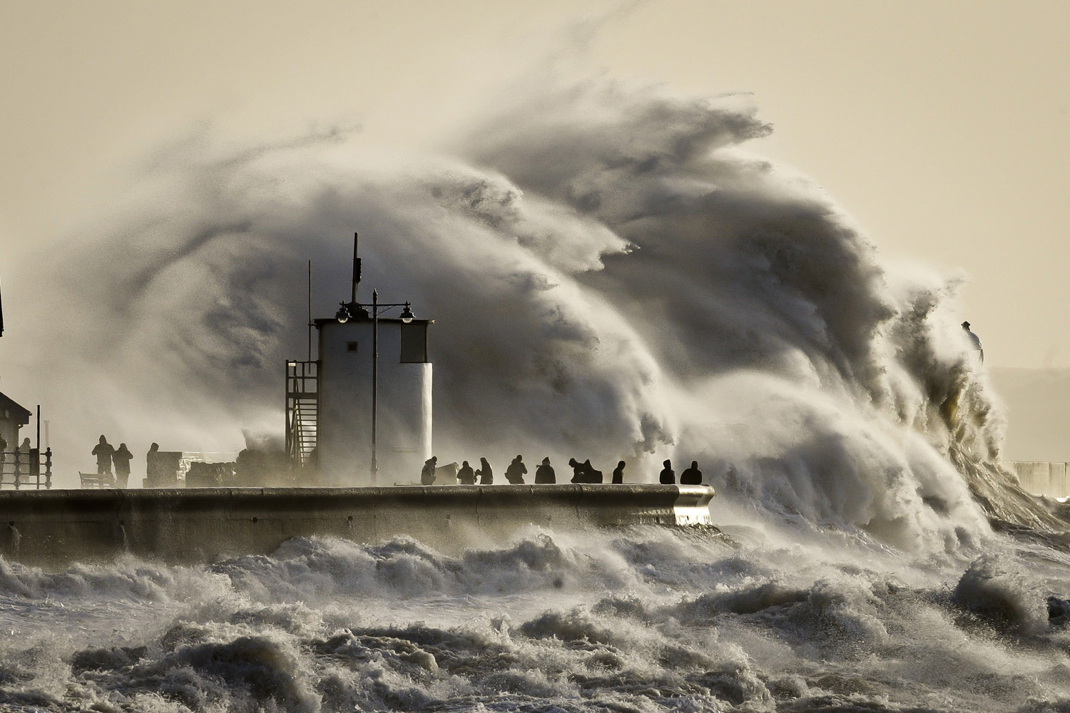 Jan. 6, 2014. People watch and photograph enormous waves as they break on Porthcawl harbour, South Wales, where very strong winds and high seas create dangerous weather conditions.