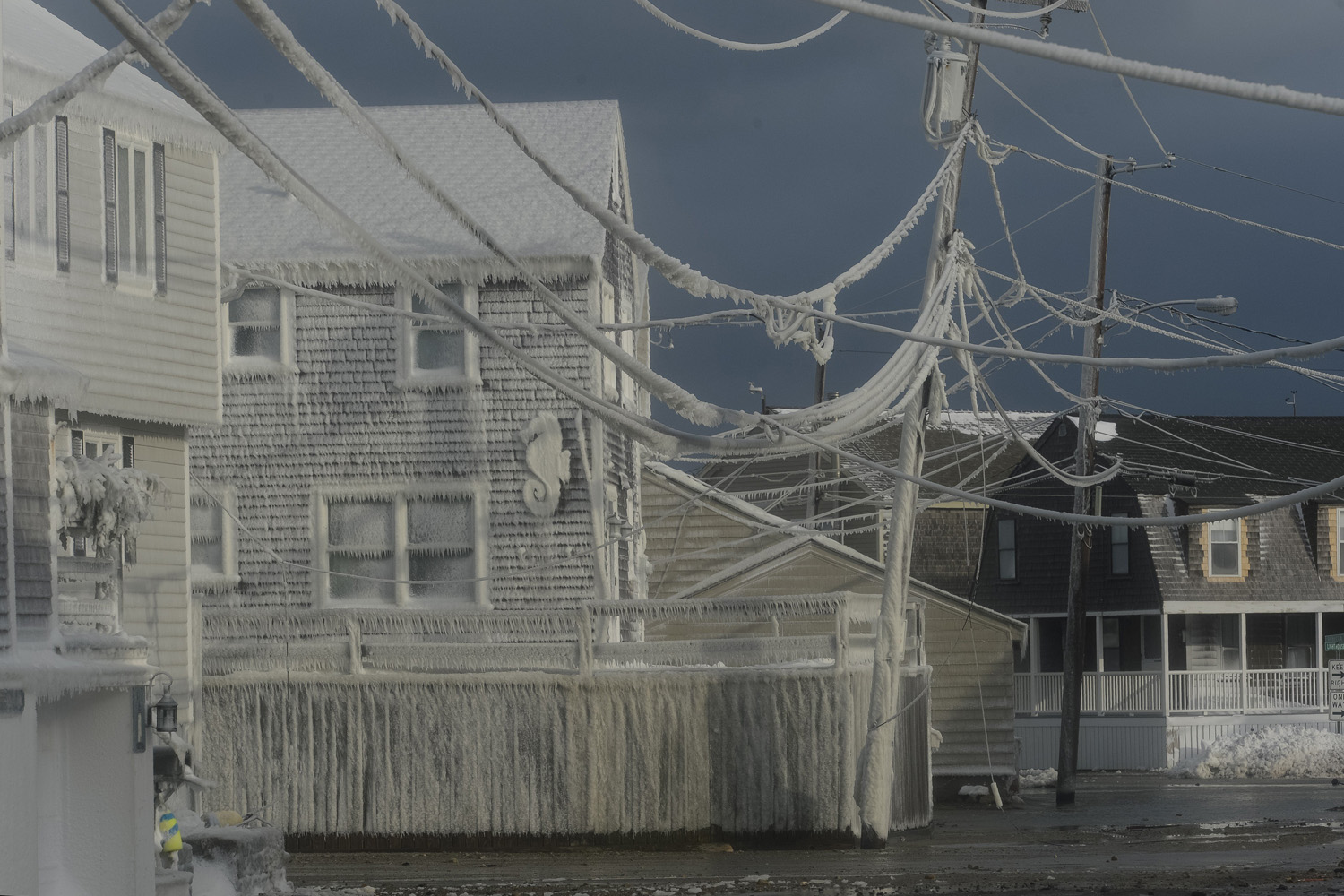 Jan. 3, 2014. Water runs down the flooded streets as homes and power lines are covered in ice from the ocean spray during the a Nor'easter winter storm in Scituate, MA.