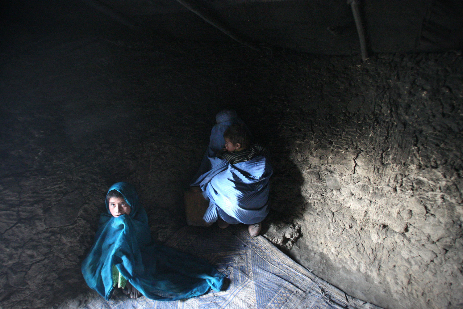 Jan. 5, 2014. An Afghan woman sits with her children at a displaced camp in Kabul.