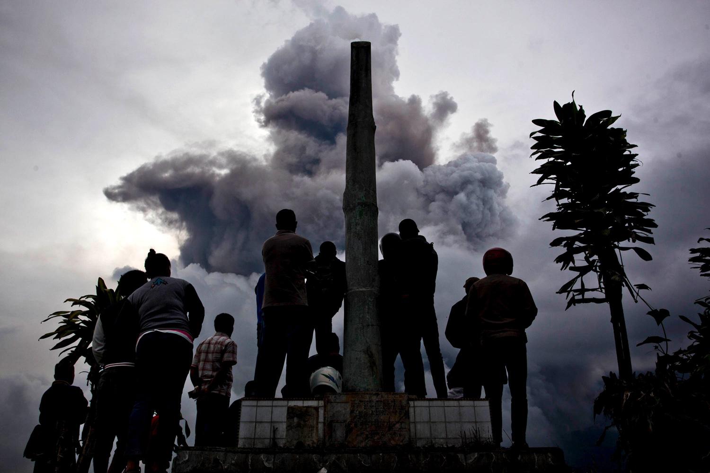 Jan. 3, 2014. People watch as Mount Sinabung spews pyroclastic smoke in Karo District, North Sumatra, Indonesia.