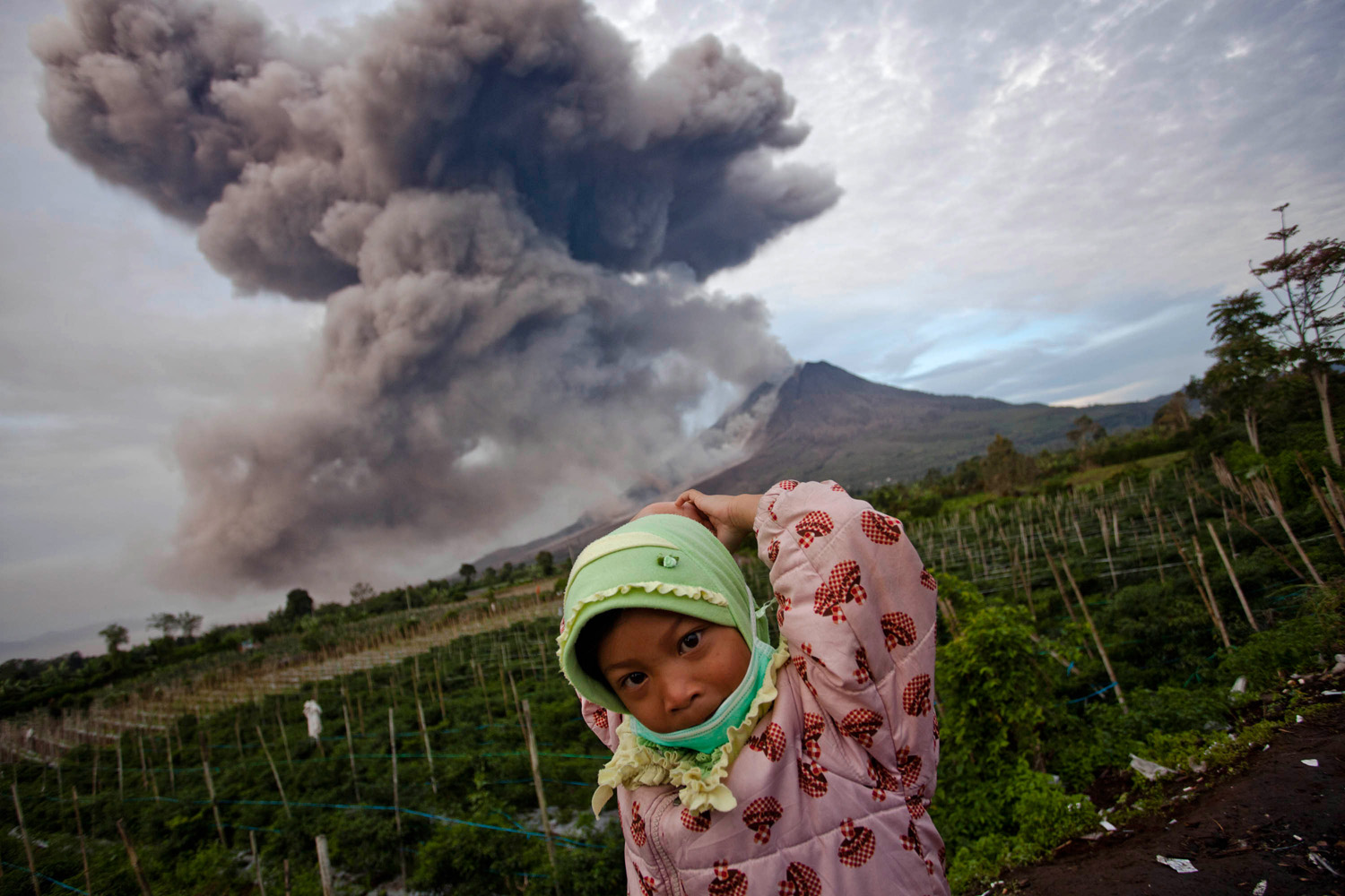 Jan. 8, 2014. A girl stands in the foreground as Mount Sinabung spews pyroclastic smoke in Karo District, North Sumatra, Indonesia.