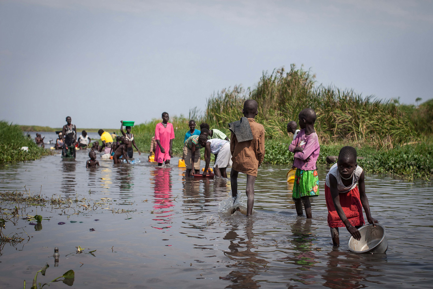 Jan. 8, 2014. Women and children crowd around a water point at dusk, in Minkammen, 25 kilometres (16 miles) south of Bor, due to lack of  water available for the thousands who have fled to Awerial region, leaving many to collect water from the Nile River, South Sudan.