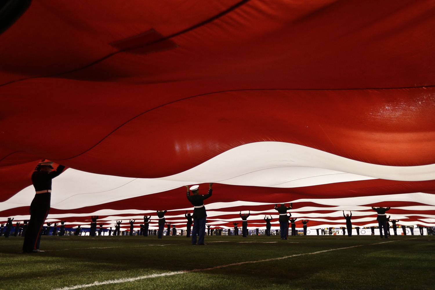 Dec. 30, 2013. United States Marines support a 100-yard American flag during pre-game ceremonies at the Holiday Bowl NCAA college football game in San Diego.