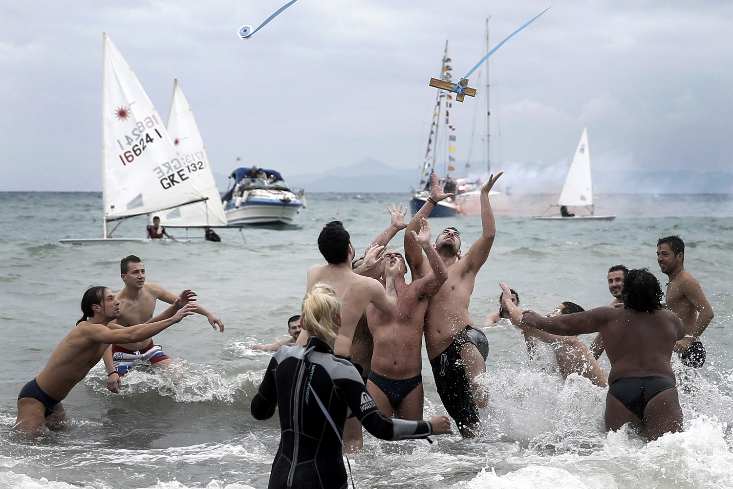 Jan. 6, 2014. A wooden cross is on the air as swimmers jump to retrieve it during a ceremony to bless the water in Greece's Flisvos beach, at Paleo Faliro near Athens.
