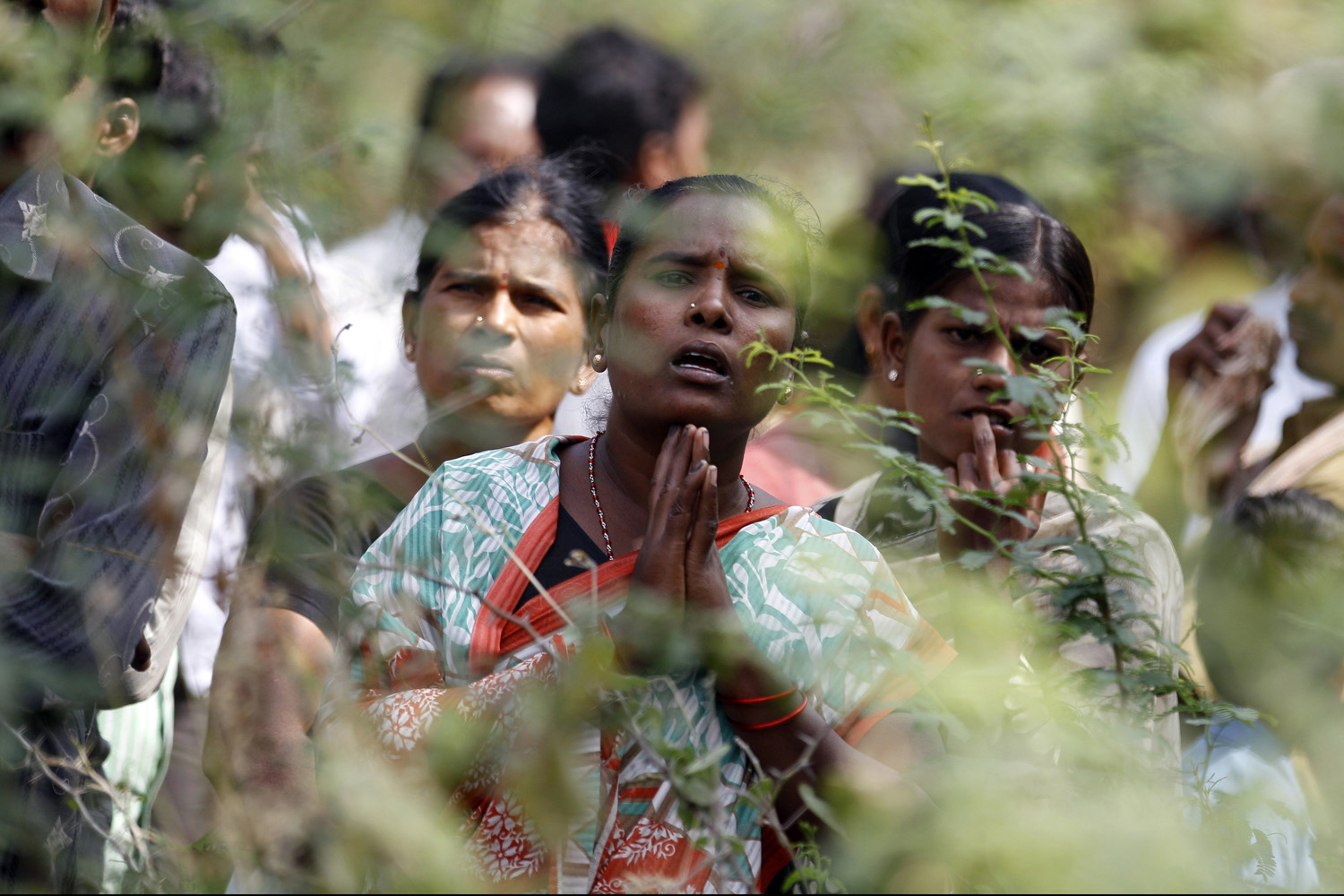 Dec. 28, 2013. An Indian woman watches with folded hands as hospital staff and volunteers carry charred bodies of passengers near the site of a train accident at Kothacheruvu, about 155 kilometers (96 miles) north of Bangalore, India.