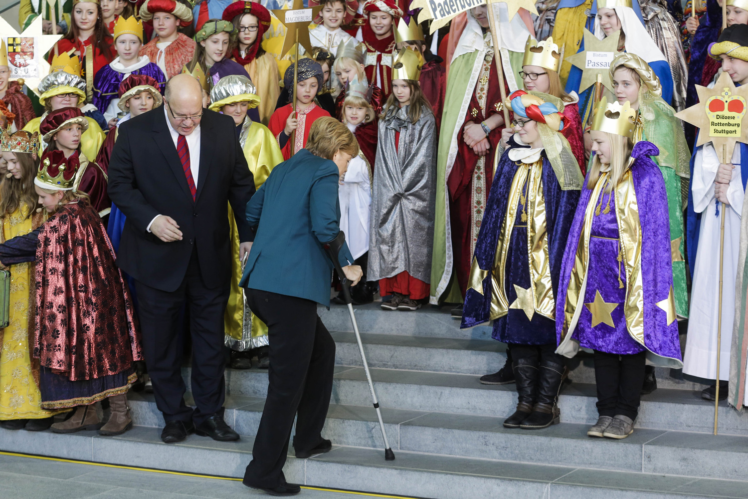 Jan. 7, 2014. The Chief Of Staff At The Chancellery Peter Altmaier, center left,  looks at German Chancellor Angela Merkel, center right, as she arrives with crutches at the annual reception for Carolers at the chancellery in Berlin.