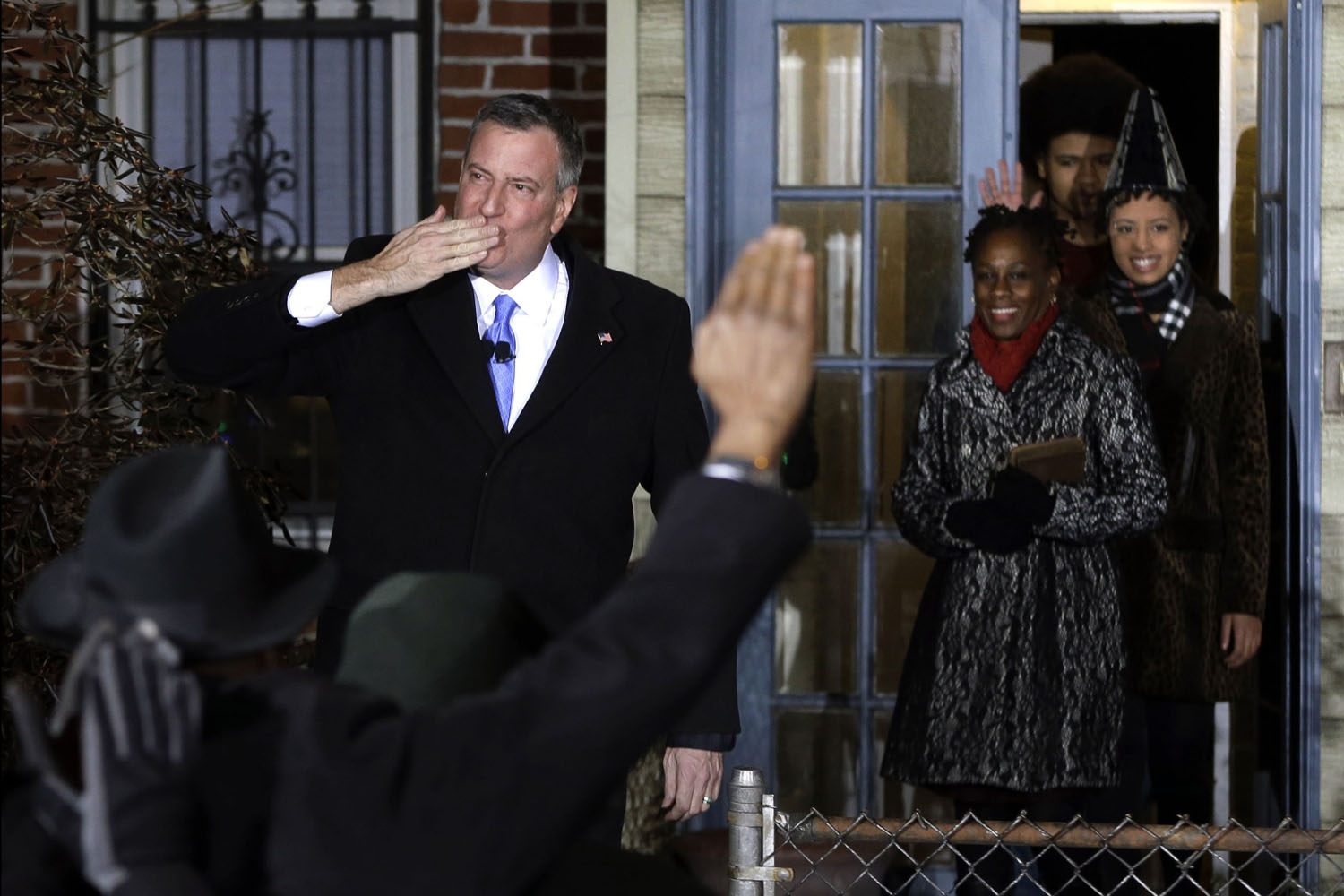 Jan. 1, 2014. Bill de Blasio blows a kiss and waves as he exits his house with his family for his swearing in ceremony as New York mayor at the start of the new year, in New York.