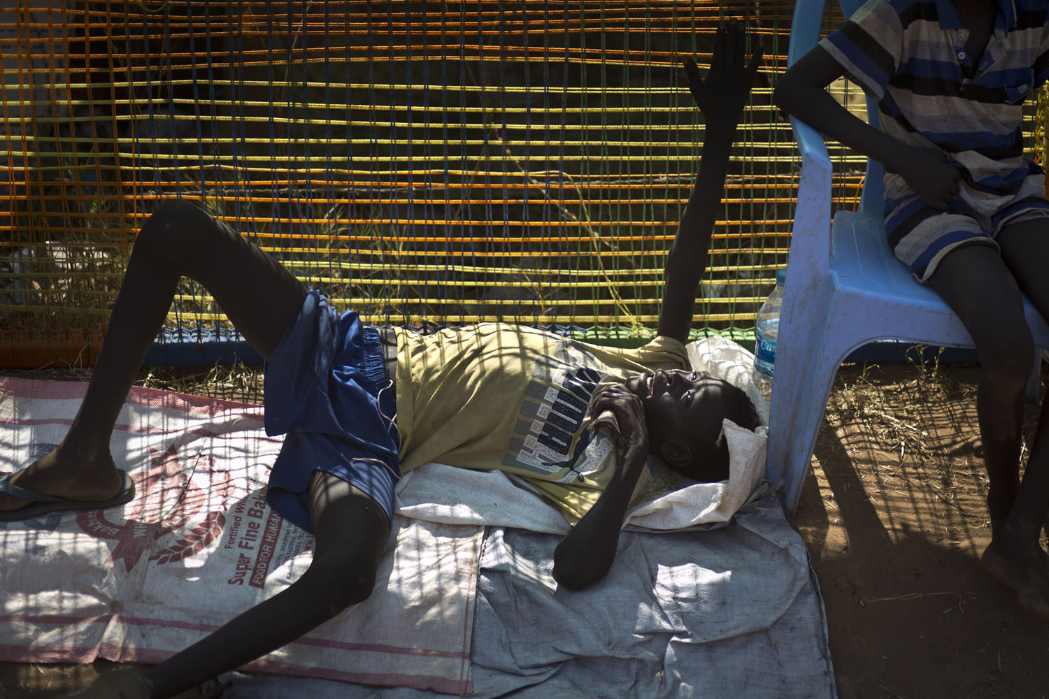 Dec. 27, 2013. A displaced boy lies down against a fence inside a United Nations compound, home to thousands of people displaced by the recent fighting in Juba, South Sudan.