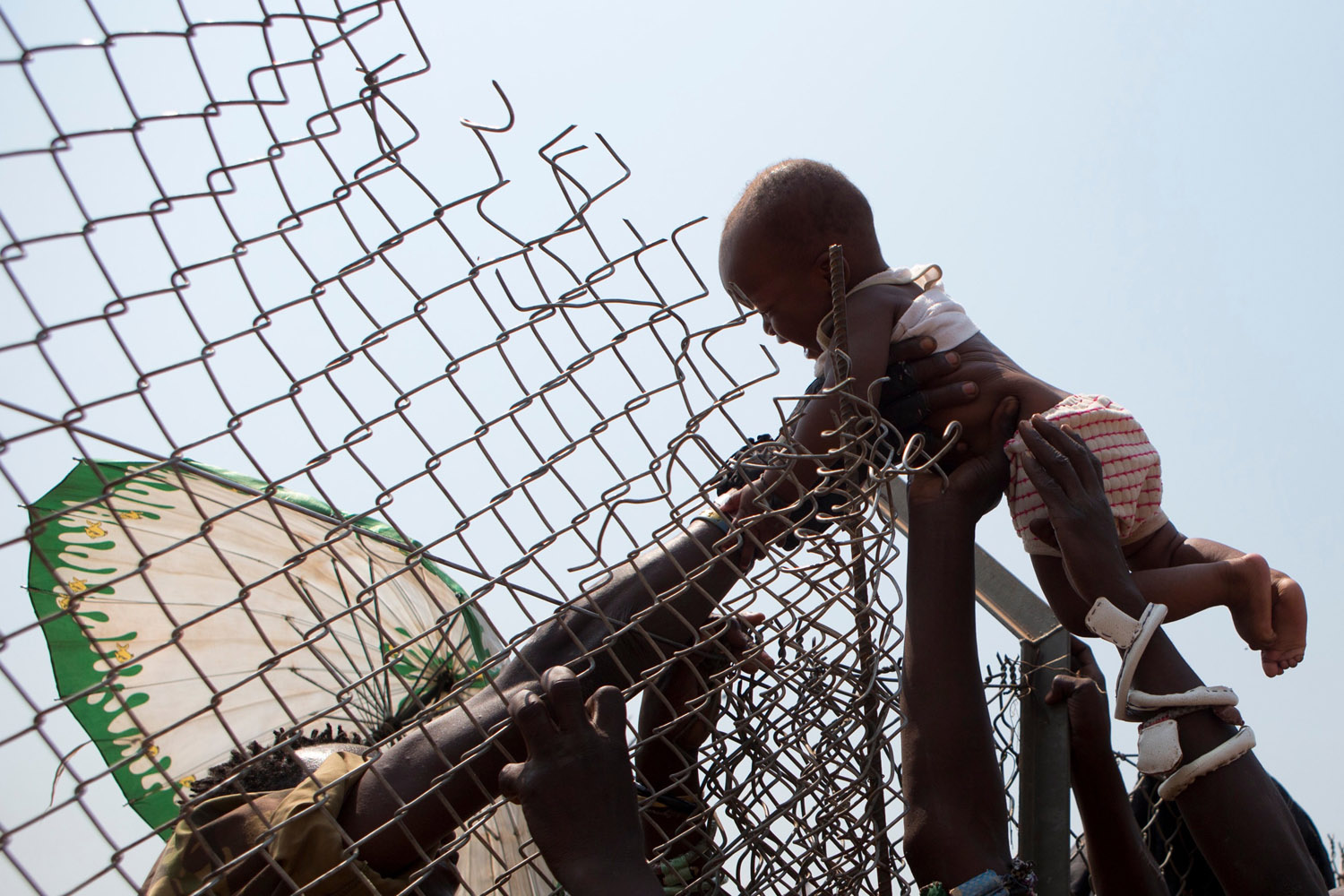 Jan. 8, 2014. A baby is passed over a high fence surrounding an aid distribution point, inside a makeshift camp housing an estimated 100,000 displaced people, at Mpoko Airport in Bangui, Central African Republic.