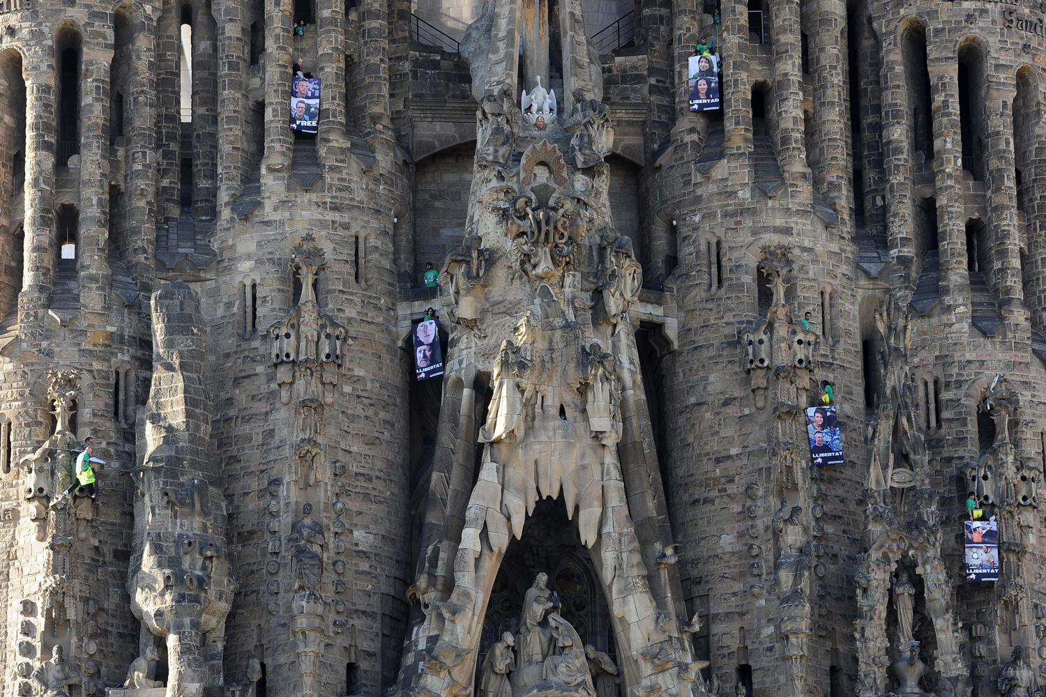 Nov. 8, 2013. In this photo provided by Greenpeace, protesters hold signs reading  Liberty  in various languages, hang from the Sagrado Familia Basilica in Barcelona, Spain.