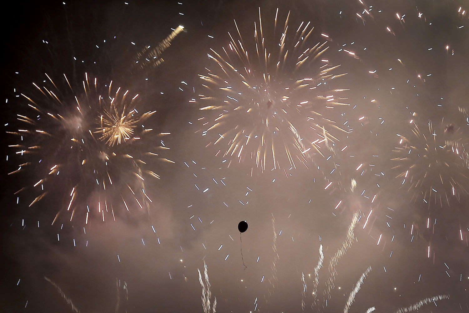 Jan. 1, 2014. A balloon floats amidst fireworks exploding over the financial district at midnight in Singapore.