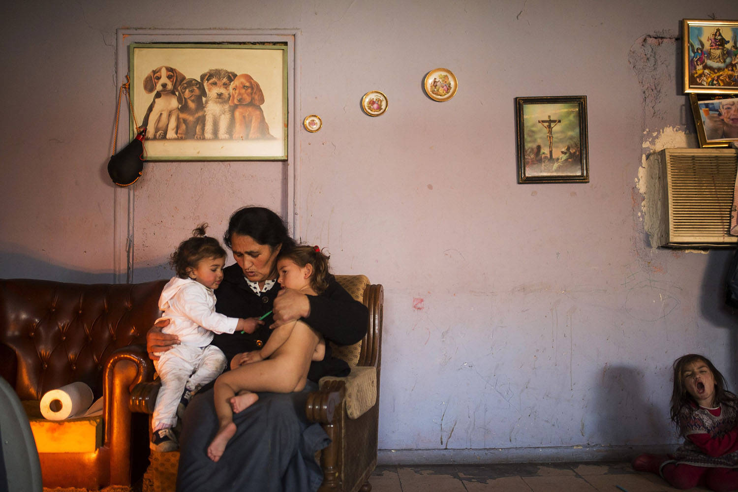 Dec. 30, 2013. Maria Jesus Navarro, 48, holds her grandchildren as they warm up next to an electric heater in the suburbs of Madrid, Spain, as the family waits to be evicted from the home they have lived in for the past ten years.
