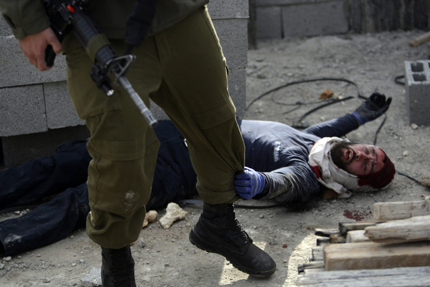 Jan. 7, 2014. An injured Israeli settler grabs an Israeli soldier's leg to get his attention after the settler was detained by Palestinian villagers in a building under construction near the West Bank village of Qusra, southeast of the city of Nablus.