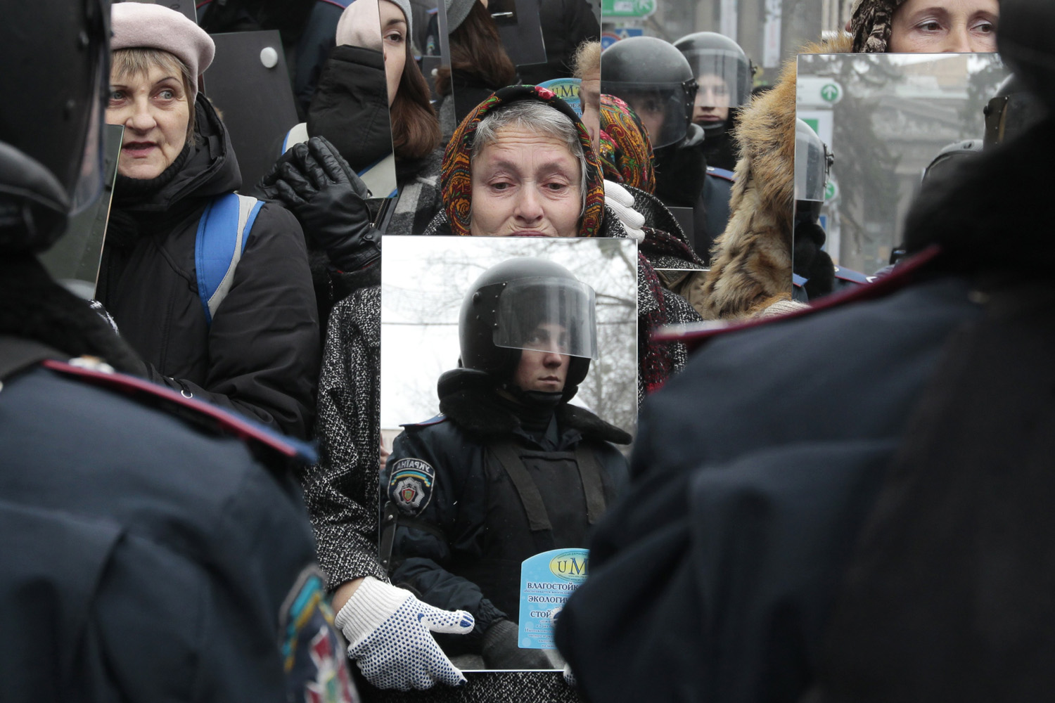 Dec. 30, 2013. A pro-European demonstrator holds a mirror which reflects a group of riot police officers standing guard in Kiev, Ukraine.