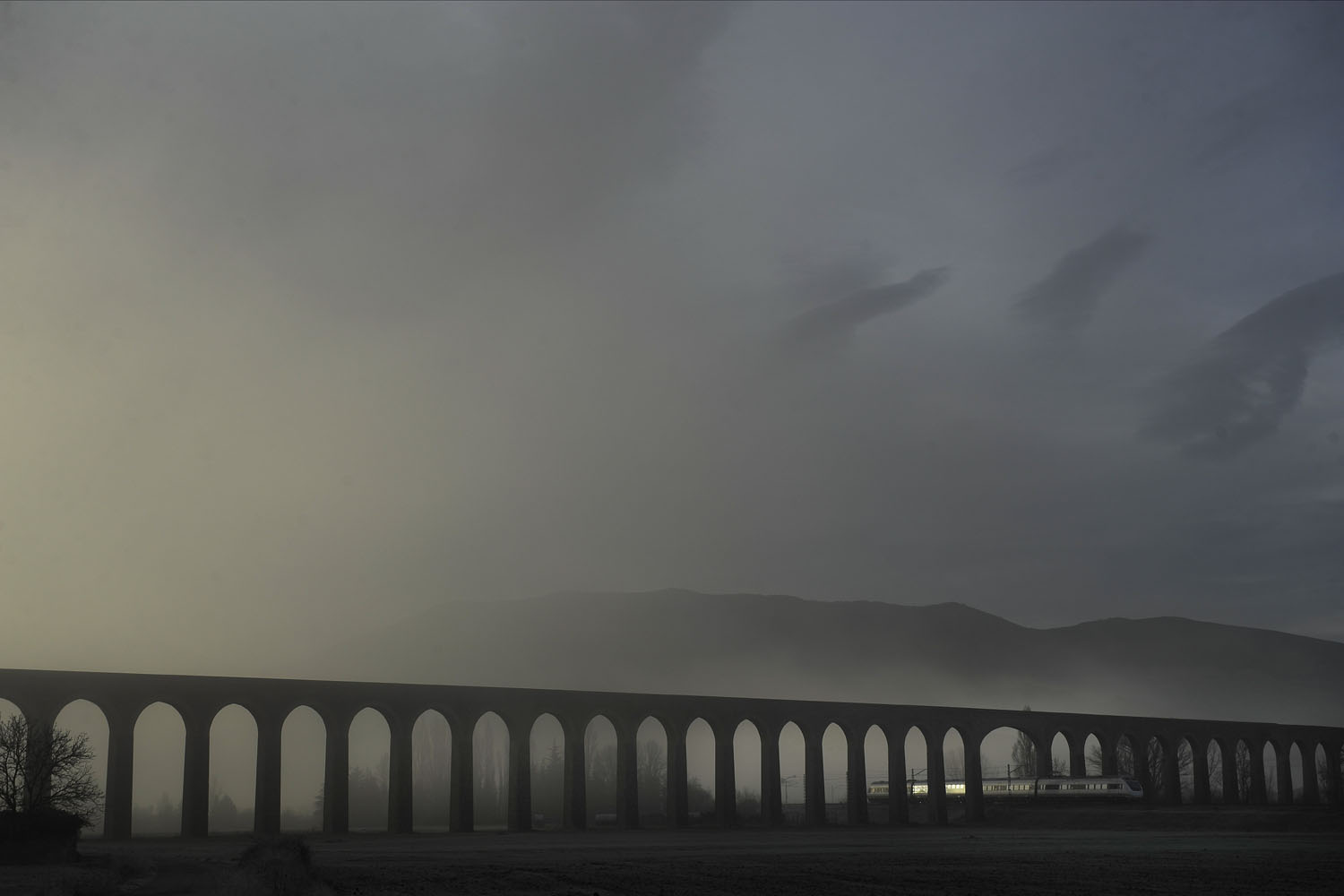 Dec. 30, 2013. The fog covers the landscape while a train crosses an ancient aqueduct, bottom right, in Noain, northern Spain.