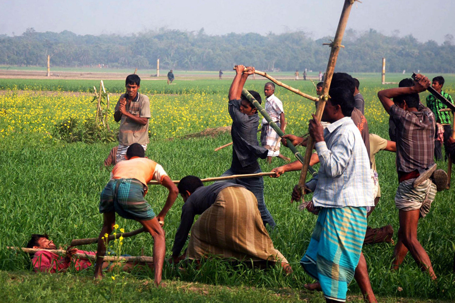 Jan. 5, 2014. A Bangladeshi resident (L) wanting to vote is attacked by protestors in a field in Rajshahi, near Dhaka.