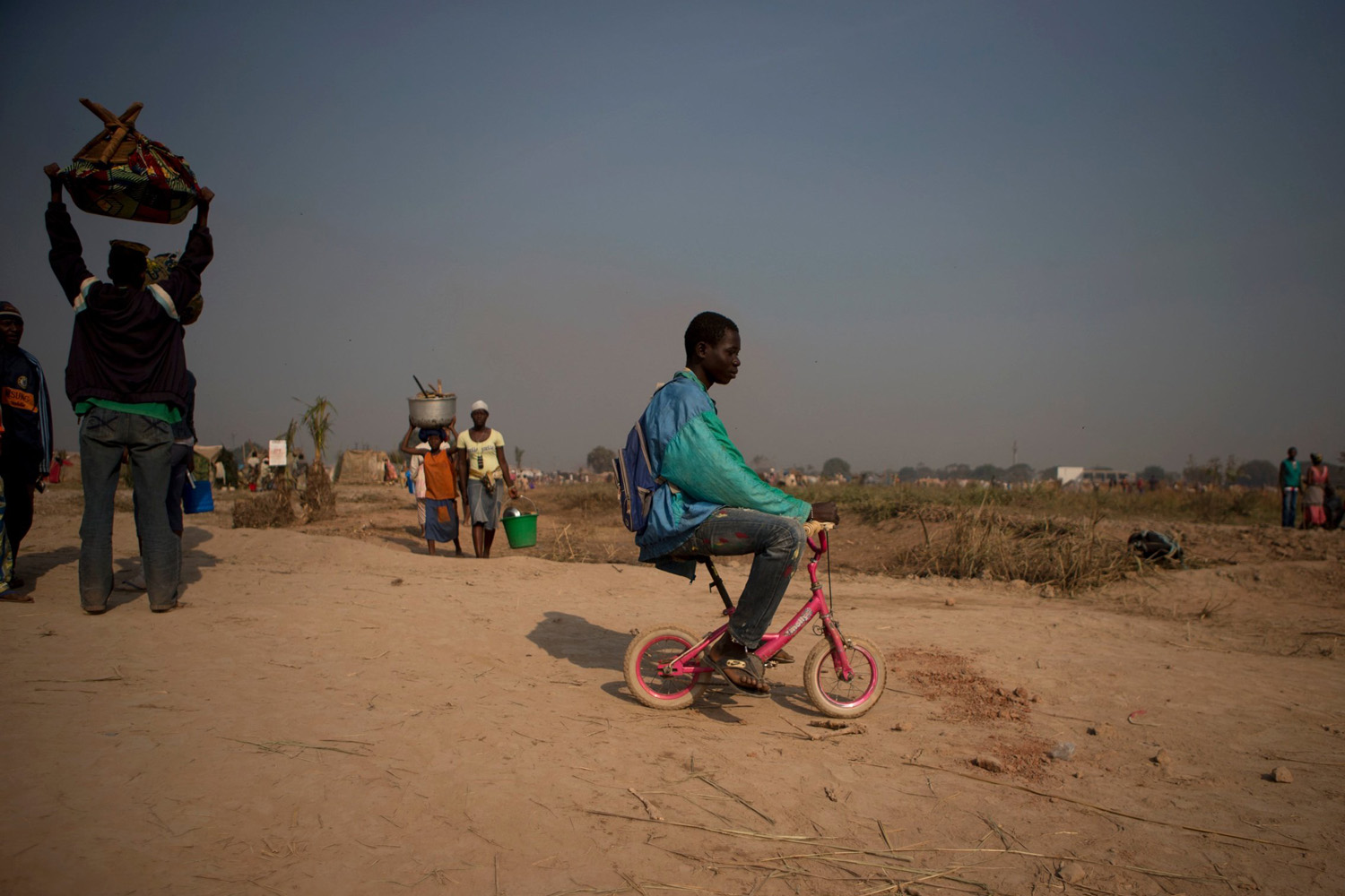 Jan. 8, 2014. A boy rides a child's bike through a new settlement area of an informal camp housing an estimated 100,000 displaced people, at Mpoko Airport in Bangui, Central African Republic.