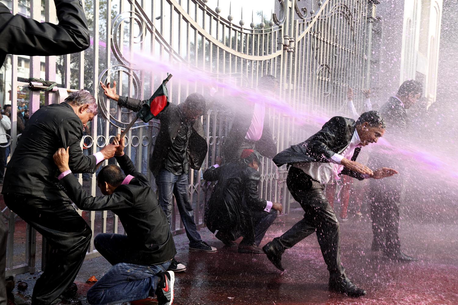 Dec. 29, 2013. Bangladesh Nationalist Party (BNP) supported lawyers are hit by a police water cannon in front of the main gate of the Supreme Court during the March For Democracy protest rally in Dhaka, Bangladesh.