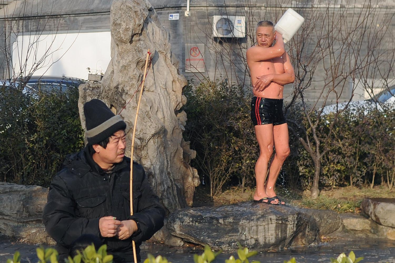Jan. 2, 2014. A Chinese ice swimmer (R) washes with water after his daily swim in Beijing, China.