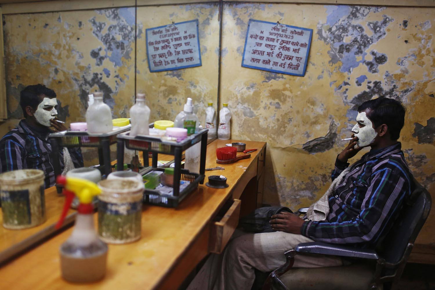 Dec. 31, 2013. A migrant laborer, his face covered with facial cream, smokes as he waits for the cream to dry at a barber shop in New Delhi, India.