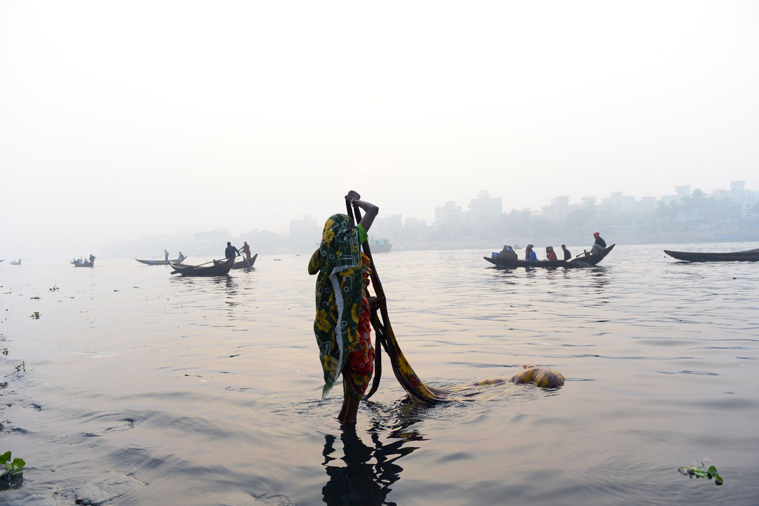 Jan. 4, 2014. A Bangladeshi resident of a depressed neighborhood washes clothing in the waters of the Buriganga river in Dhaka.